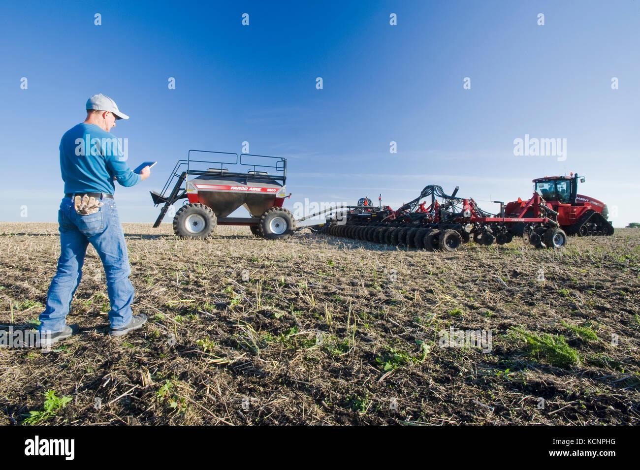 Landwirt mit einem Tablet vor einem Traktor und pneumatische Sämaschine Aussaat Winterweizen in einem Null Stockbild