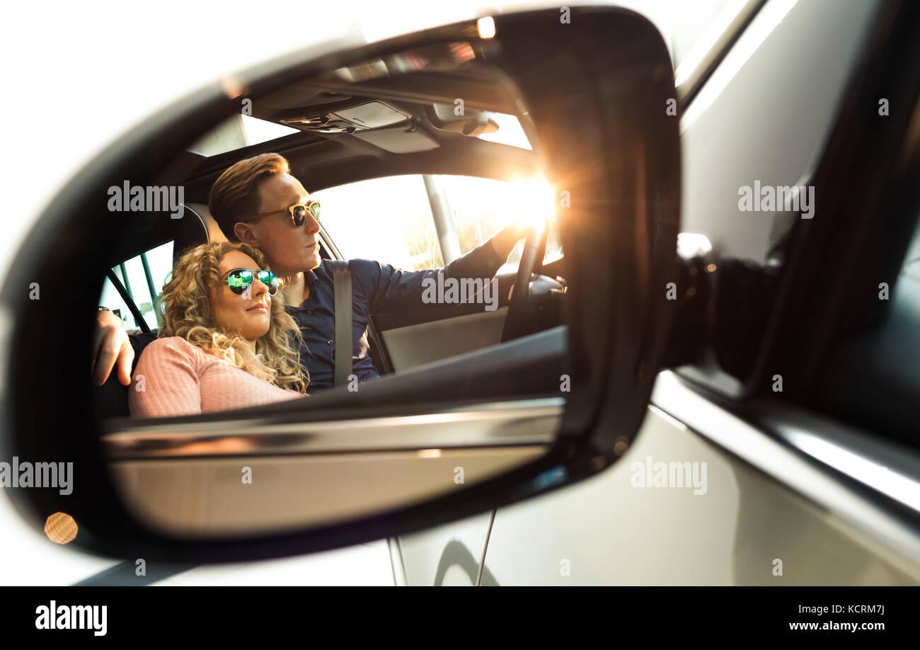 Paar in Seitenansicht Spiegel der Auto während der Probefahrt widerspiegelt Stockbild