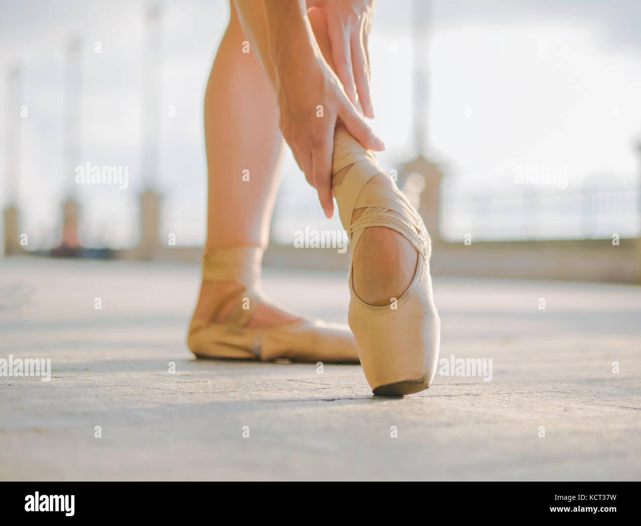Nahaufnahme der Füße ist ein Tänzer, wie sie Praktiken Übungen auf dem Stein Damm pointe. Woman's Füße in Pointe Stockfoto