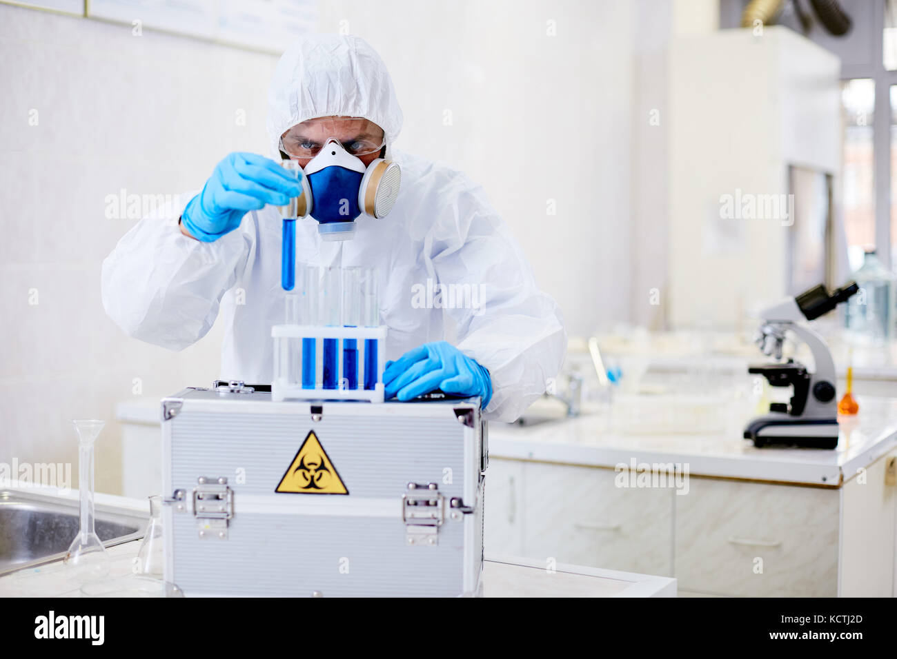 Talentierte Virologie Wissenschaftler tragen einen Schutzanzug und Atemschutz arbeiten mit biohazard Substanz während Stockbild
