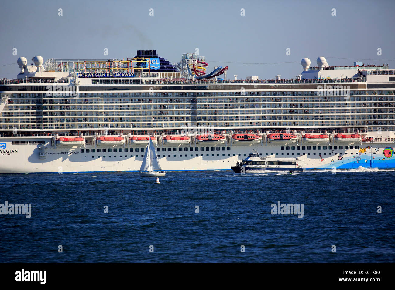 Norwegische Abreiß-Kreuzfahrtschiff in den Hudson River mit Segelboot im Vordergrund. new york city, usa. Stockbild