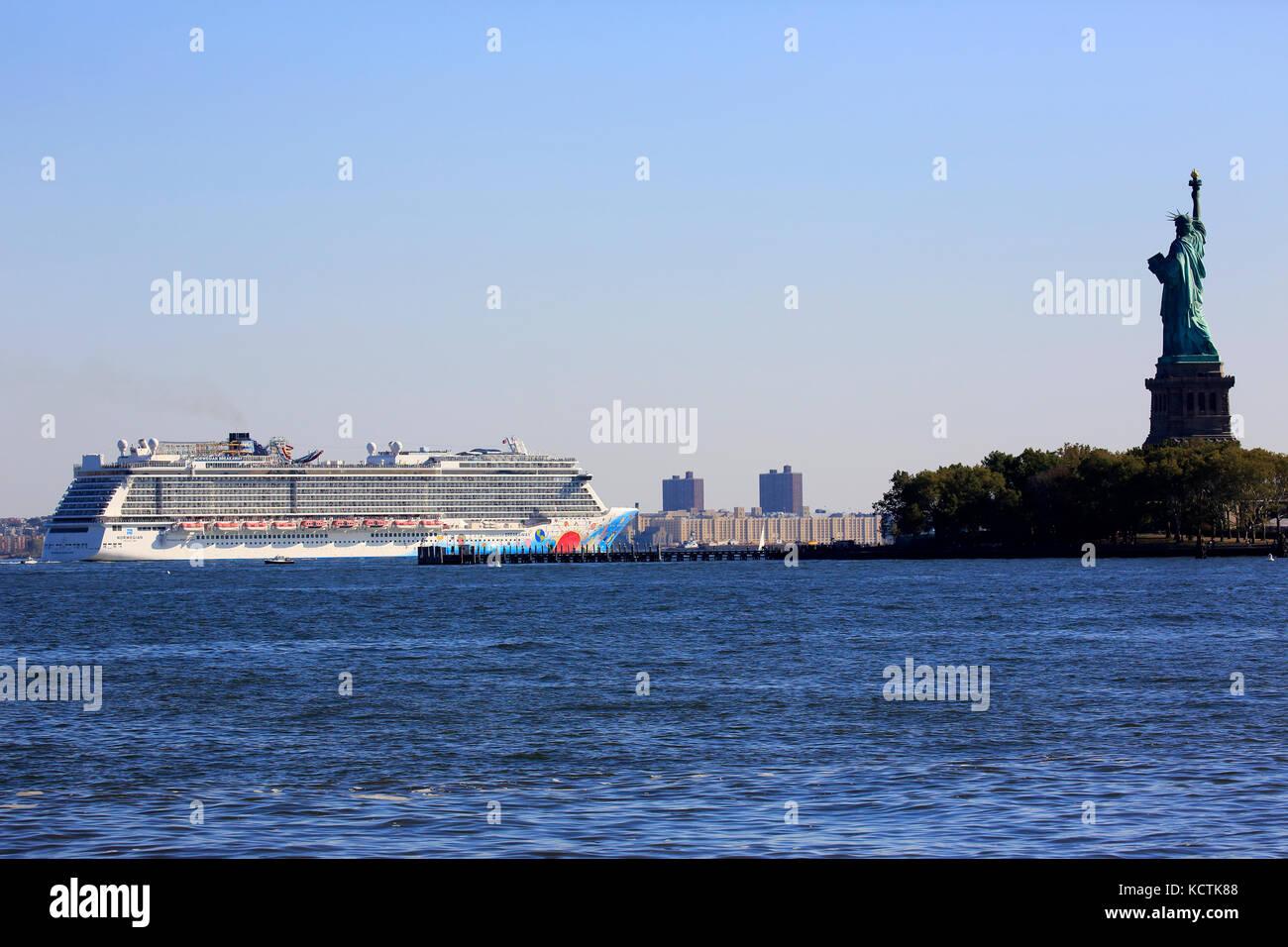 Norwegische Abreiß-Kreuzfahrt vorbei an Liberty Island mit der Freiheitsstatue neben in den Hafen von New York. Stockbild