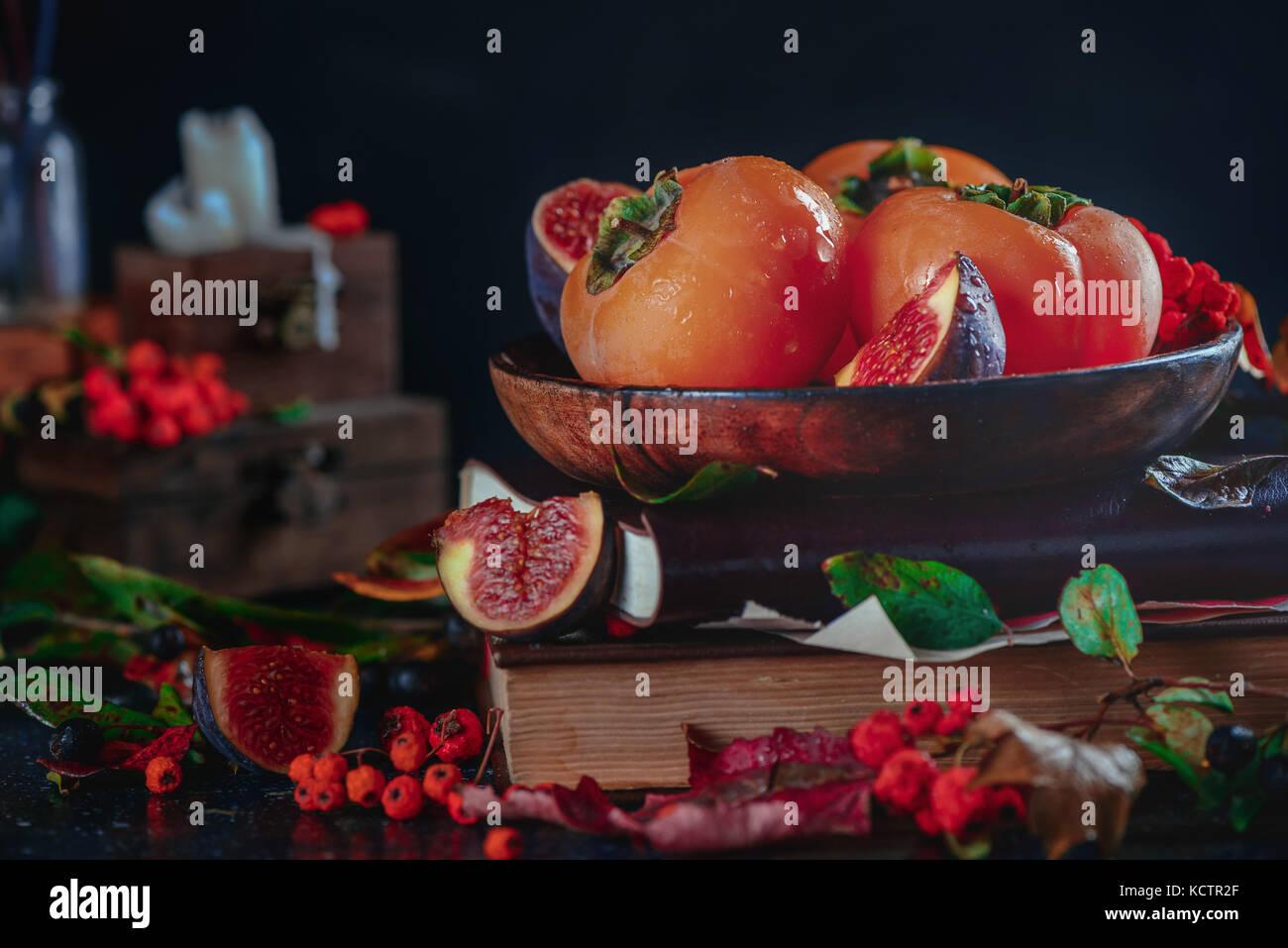 Reife persimonen auf einem Stapel Bücher in einem dunklen Herbst Stillleben mit Früchten und Beeren. Ernte Stockbild