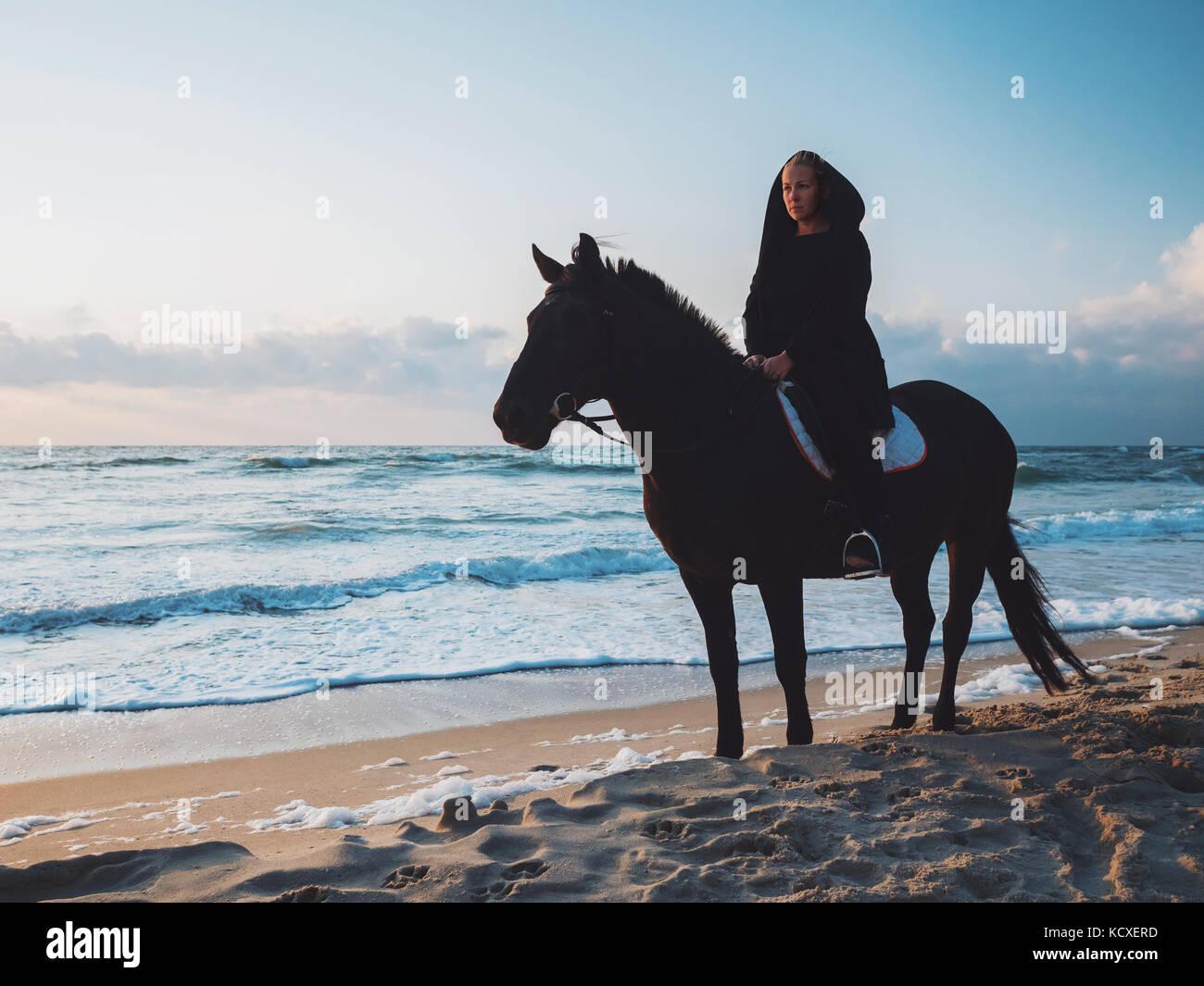 shof von frau sitzt auf einem schwarzen pferd auf dem meer. Black Bedroom Furniture Sets. Home Design Ideas