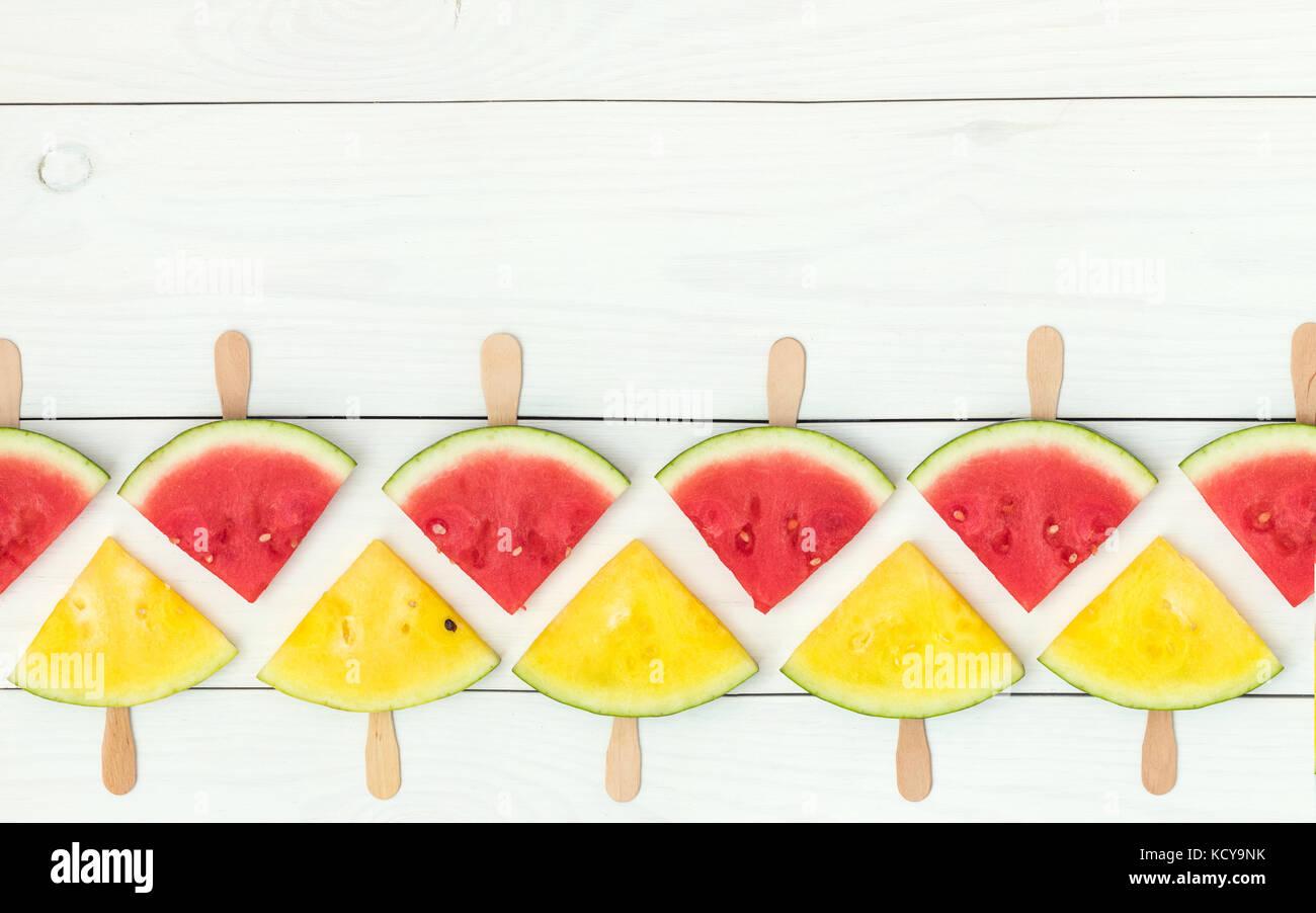 Rote und gelbe Wassermelone auf Holzstäbchen auf einem weißen Hintergrund. Holz flach, Ansicht von oben, Stockbild