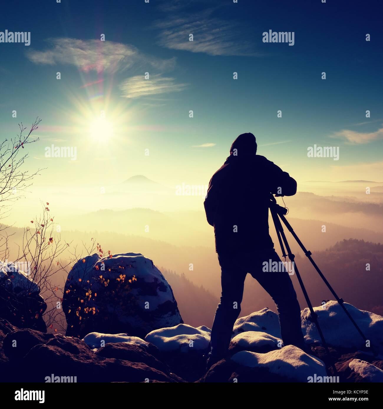 Professioneller Fotograf nimmt Bild von Freeze herbstliche Tagesanbruch, Felsen, bedeckt mit frischem Pulverschnee. Stockbild
