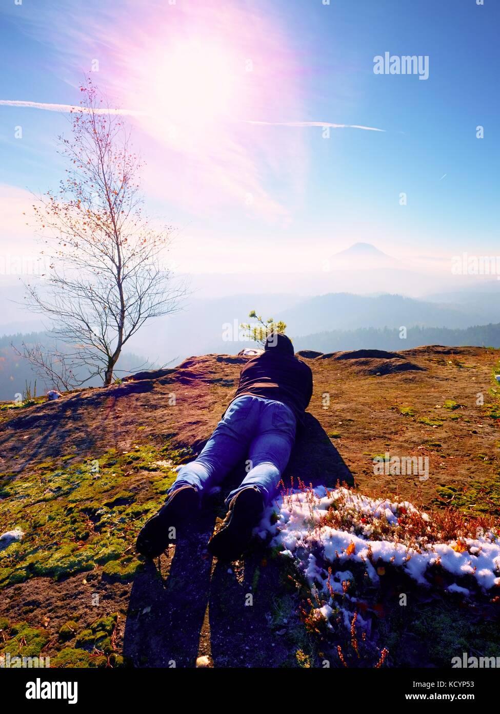 Mann legt und unter Foto von Spiegel Kamera am Hals. Snowy felsigen Gipfel des Berges. professioneller Fotograf Stockbild