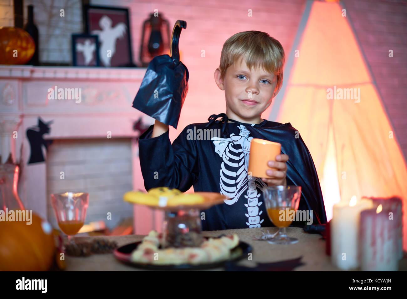 Cute little boy tragen Skelett Kostüm mit Kerze in der Hand, während ...