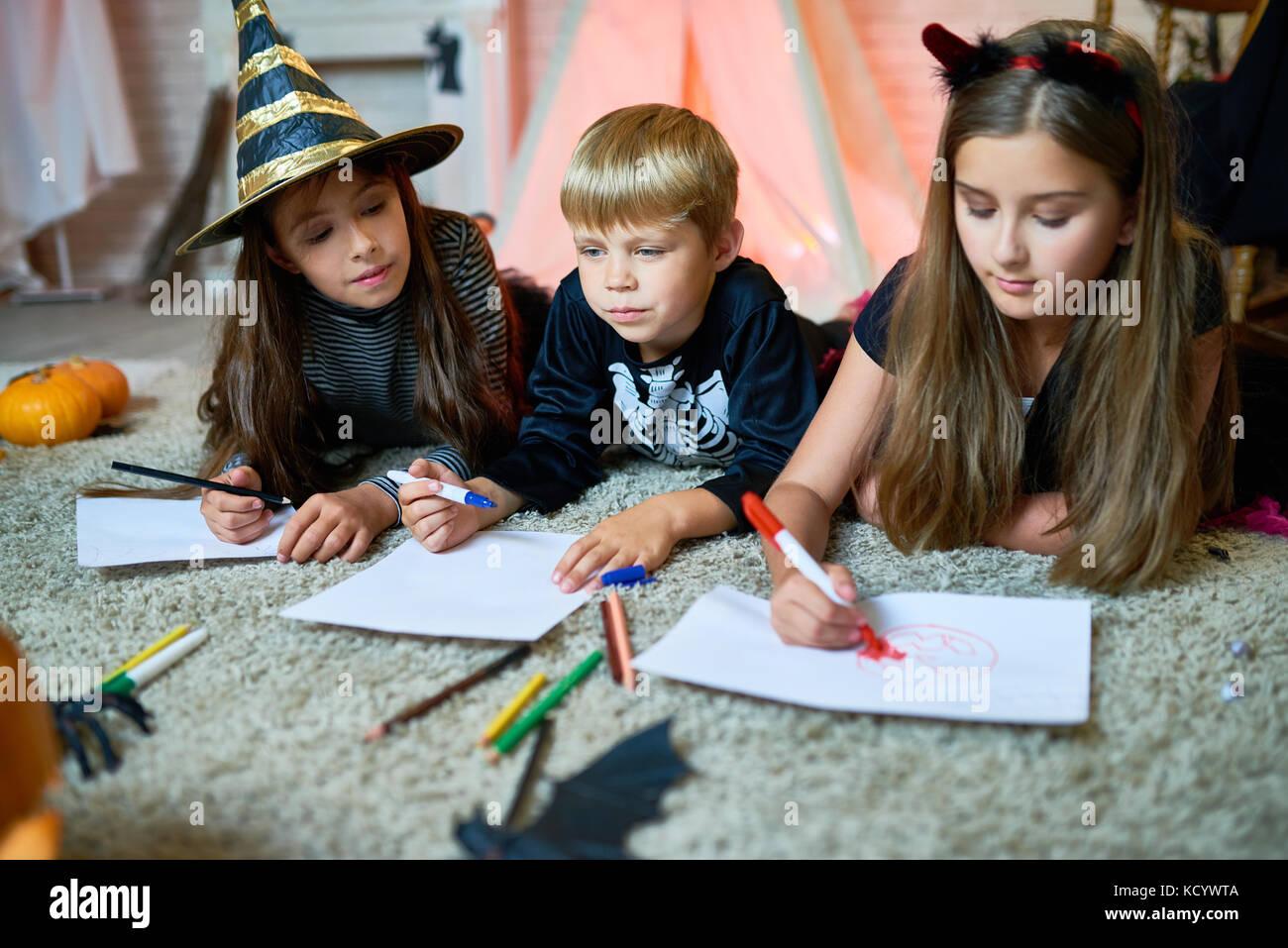 Süße kleine Freunde tragen phantastische Kostüme auf gemütlichen Teppich im Wohnzimmer für Stockbild