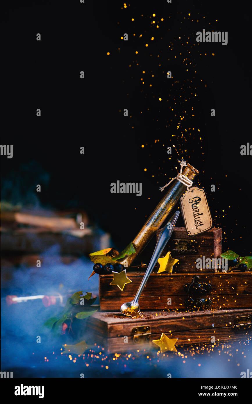 Stardust Reagenzglas mit Kisten aus Holz in einer magischen Stillleben mit goldenen Glitzer und Sterne. wizard Tabelle Stockbild