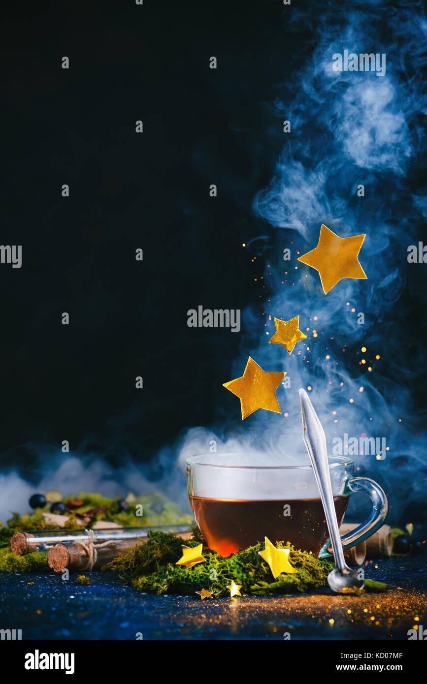 Eine Tasse Kaffee mit dichten Dampf, einem antiken Löffel, goldene Sterne und magische pixie staub auf einem Stockbild
