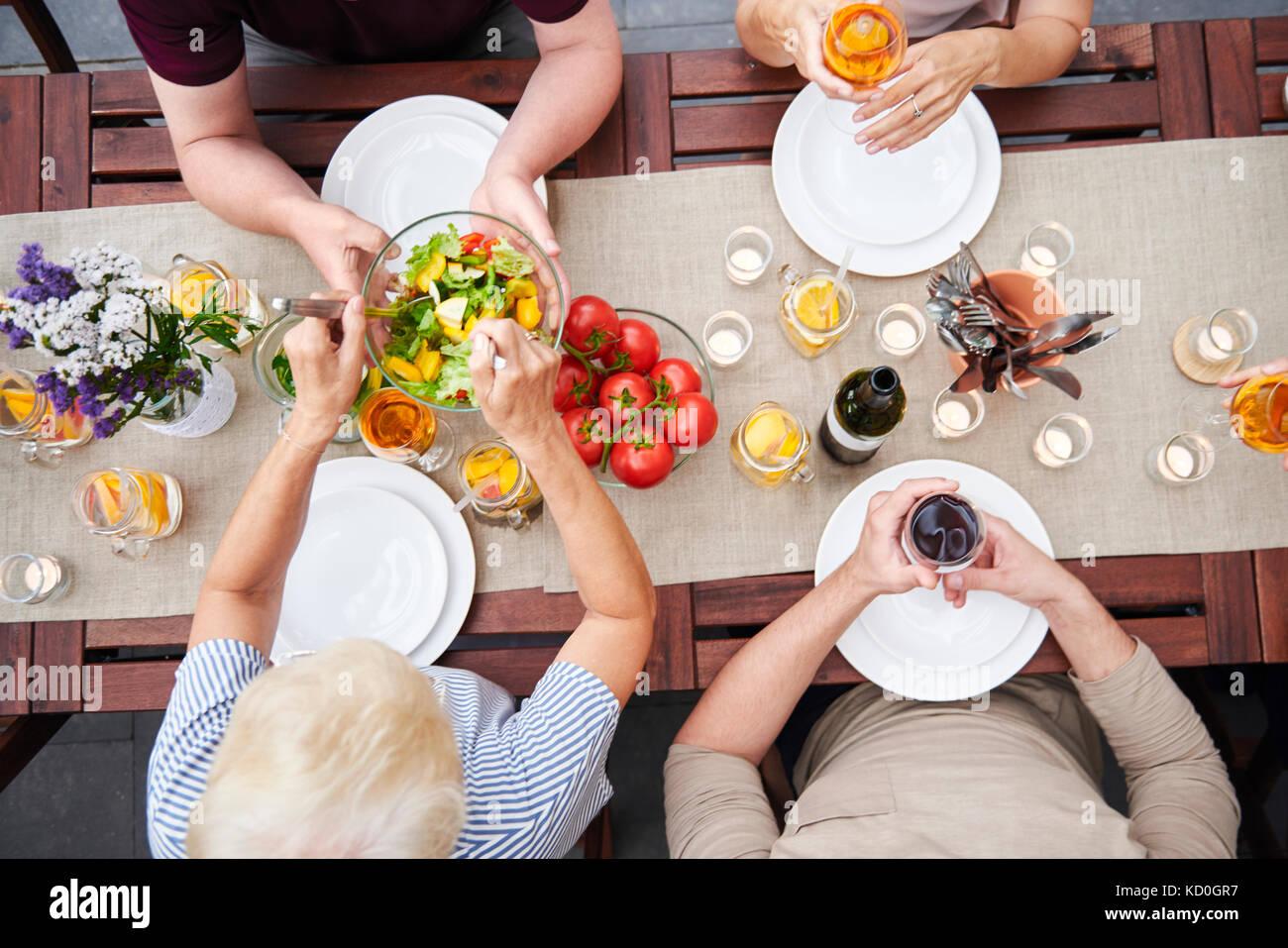 Ansicht von oben der Familie übergabe Salate bei Familie Mittagessen auf der Terrasse Stockbild