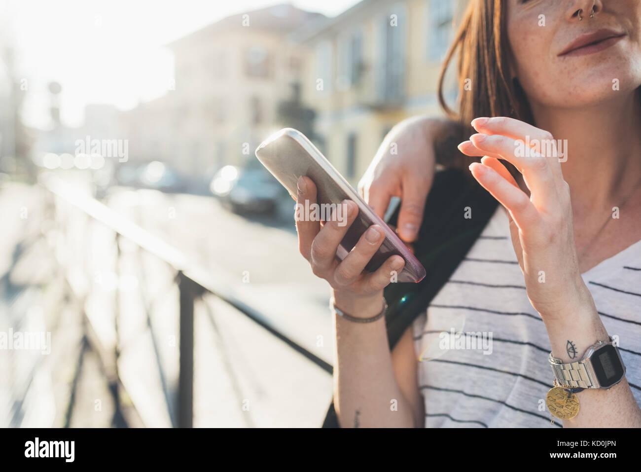 7/8 Schuß von Paar auf dem Bürgersteig auf Smartphone Stockbild