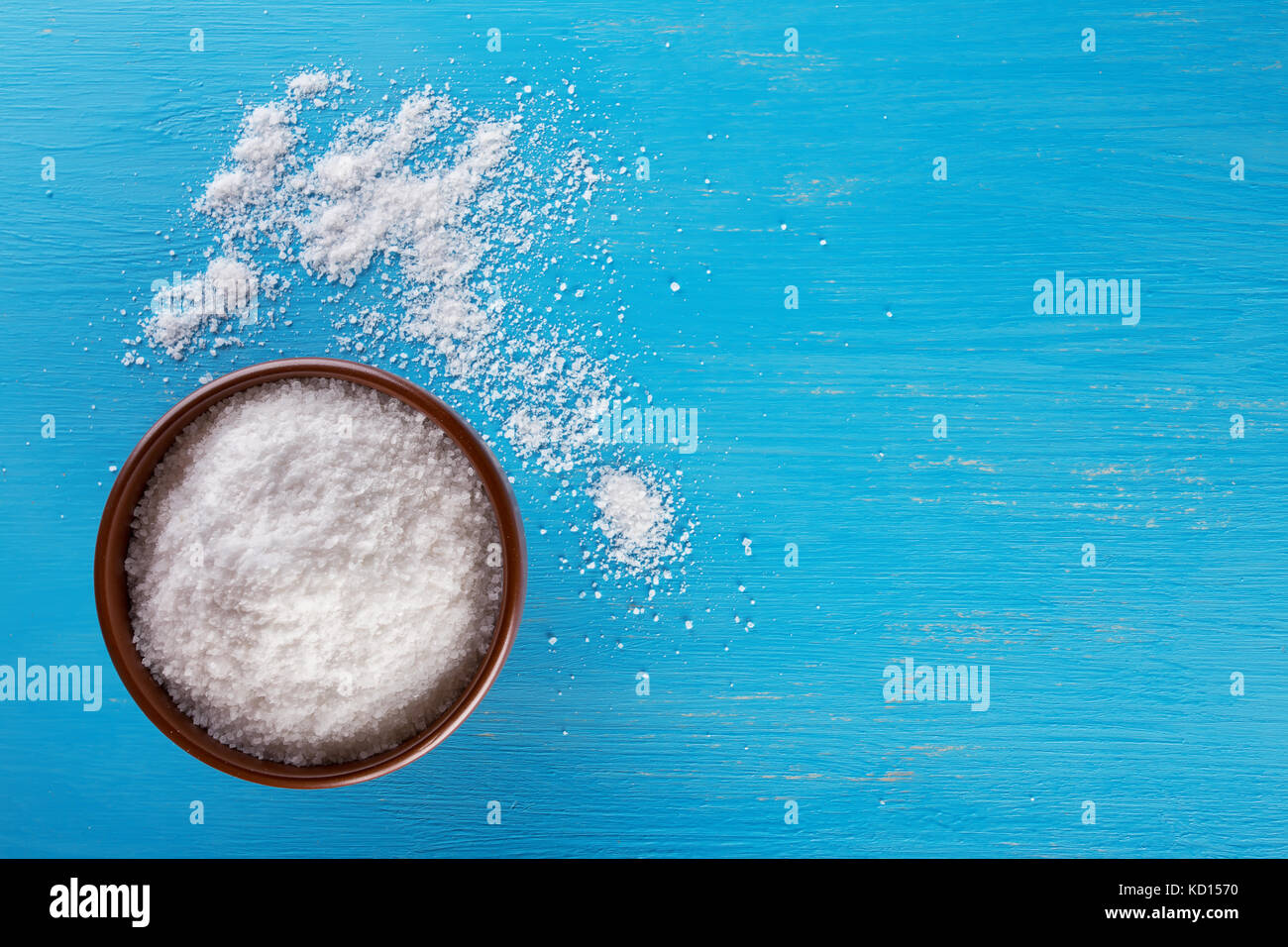 Clay brown Schüssel mit Salz auf blauem Hintergrund Stockbild