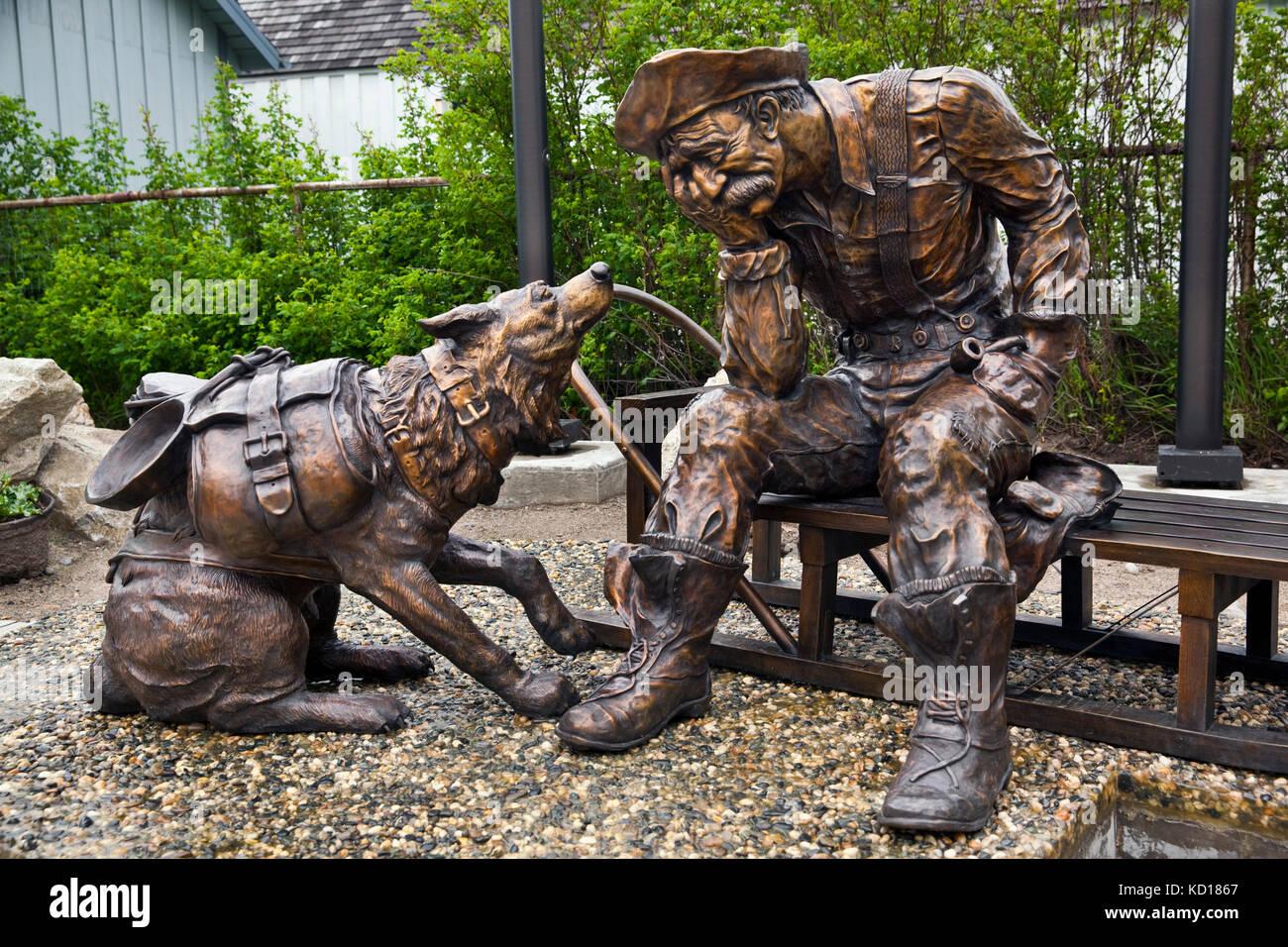 """Bronze Mensch und Hund, die Teil einer Installation im Außenbereich mit dem Titel """"Tonne"""" und zum Stockbild"""