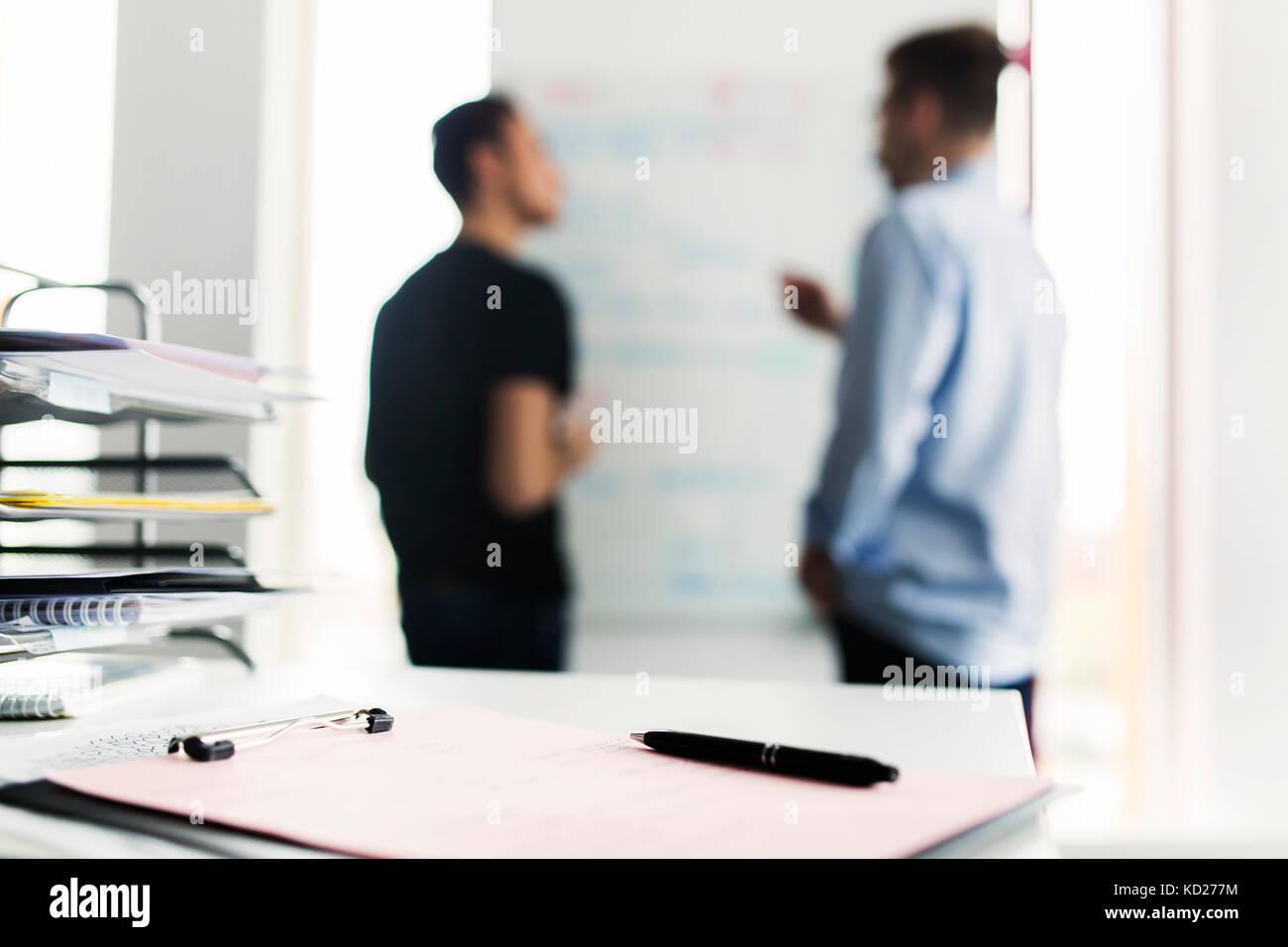 Zwischenablage mit Pen, Kollegen im Hintergrund Stockbild