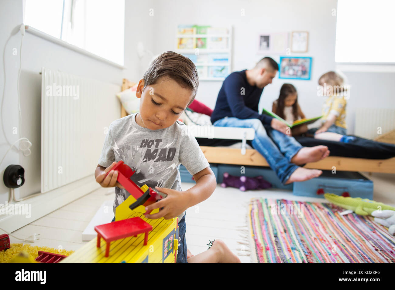 Vater und Kinder (2-3, 6-7) spielen im Zimmer Stockfoto