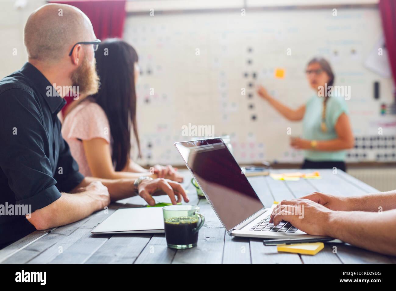 Mitarbeiter, Kollegen zeigen auf Whiteboard Stockbild