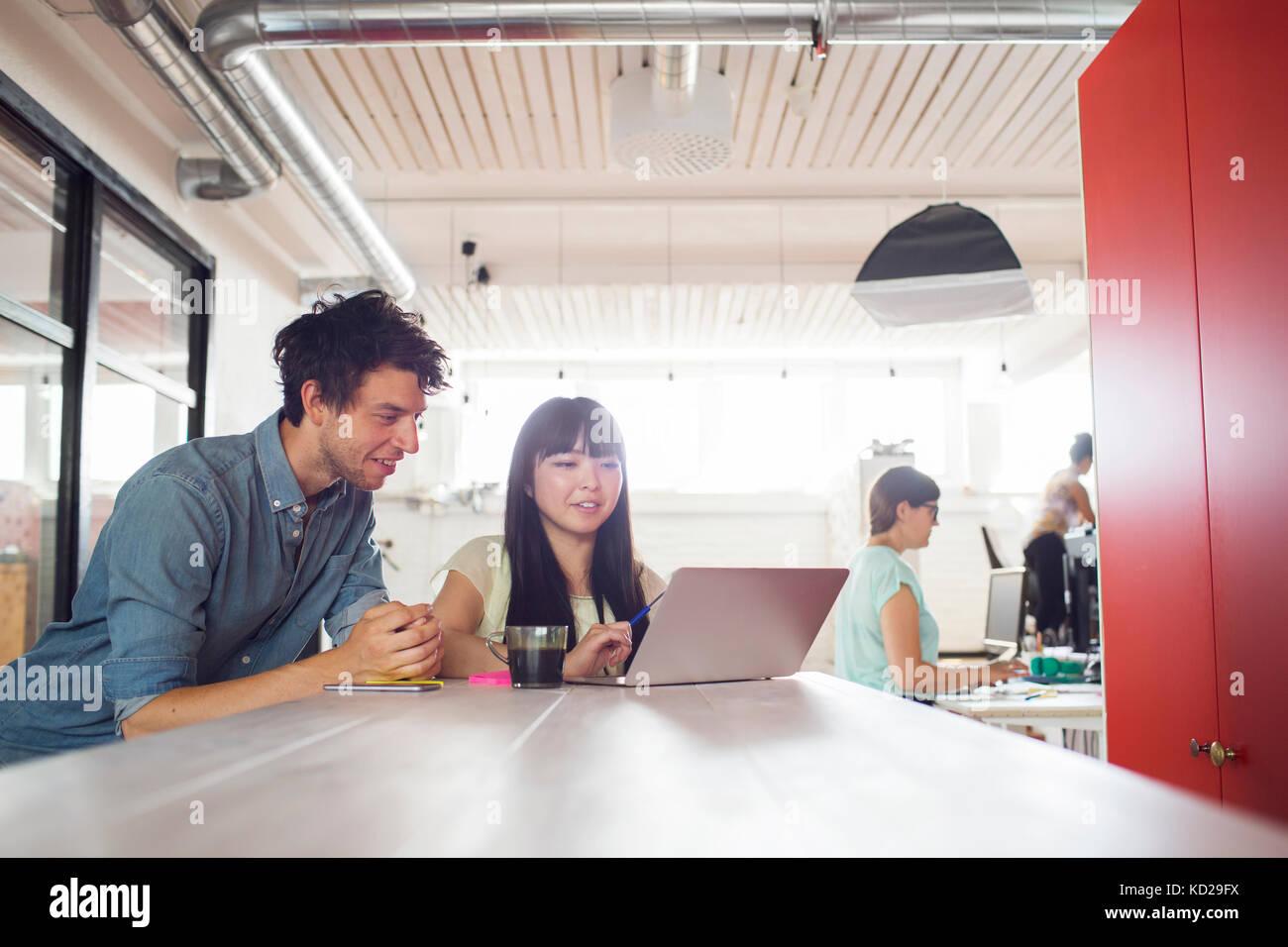 Mann und zwei Frauen auf die Arbeit im Büro, Frau, die durch die Fenster im Hintergrund Stockfoto