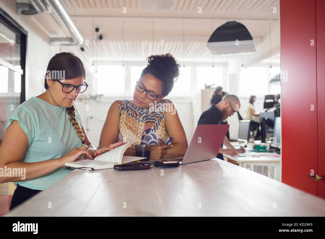 Frauen, die durch die Tabelle im Büro, Mitarbeiter im Hintergrund Stockfoto