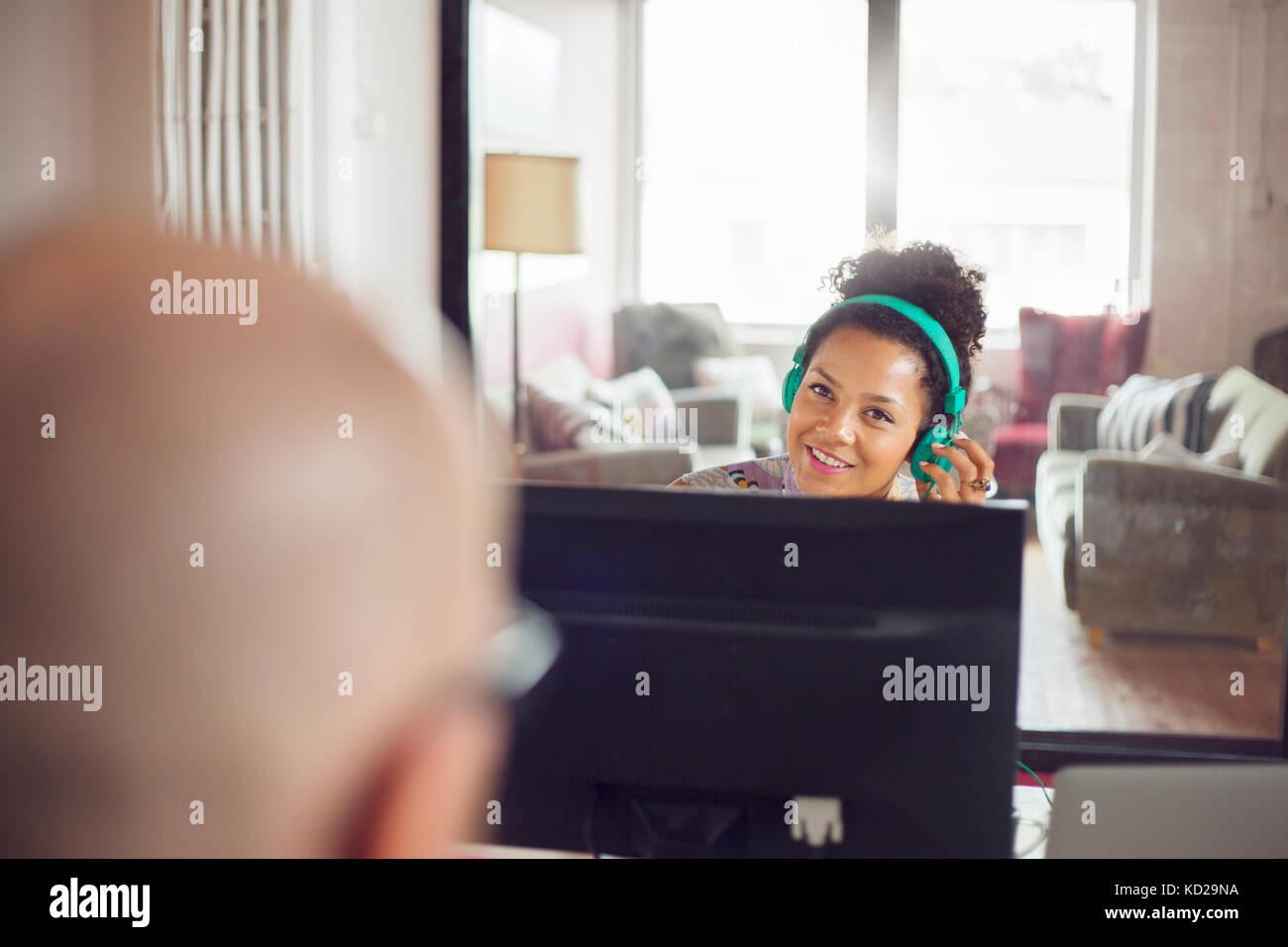 Frau mit Kopfhörern zu sprechen glatzköpfige Mann und lächelnd Stockfoto