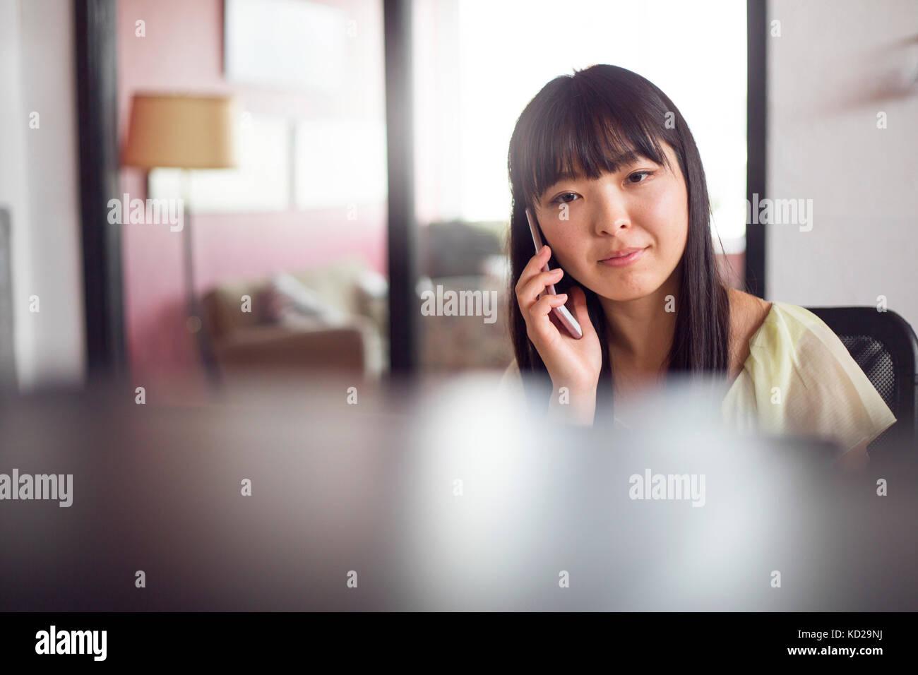 Frau mit Phone im Büro Stockbild