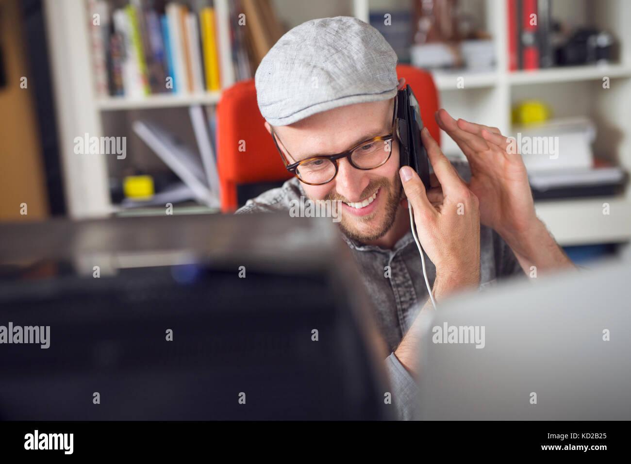 Mitte der erwachsene Mann lächelnd, während Sie das Telefon Stockbild