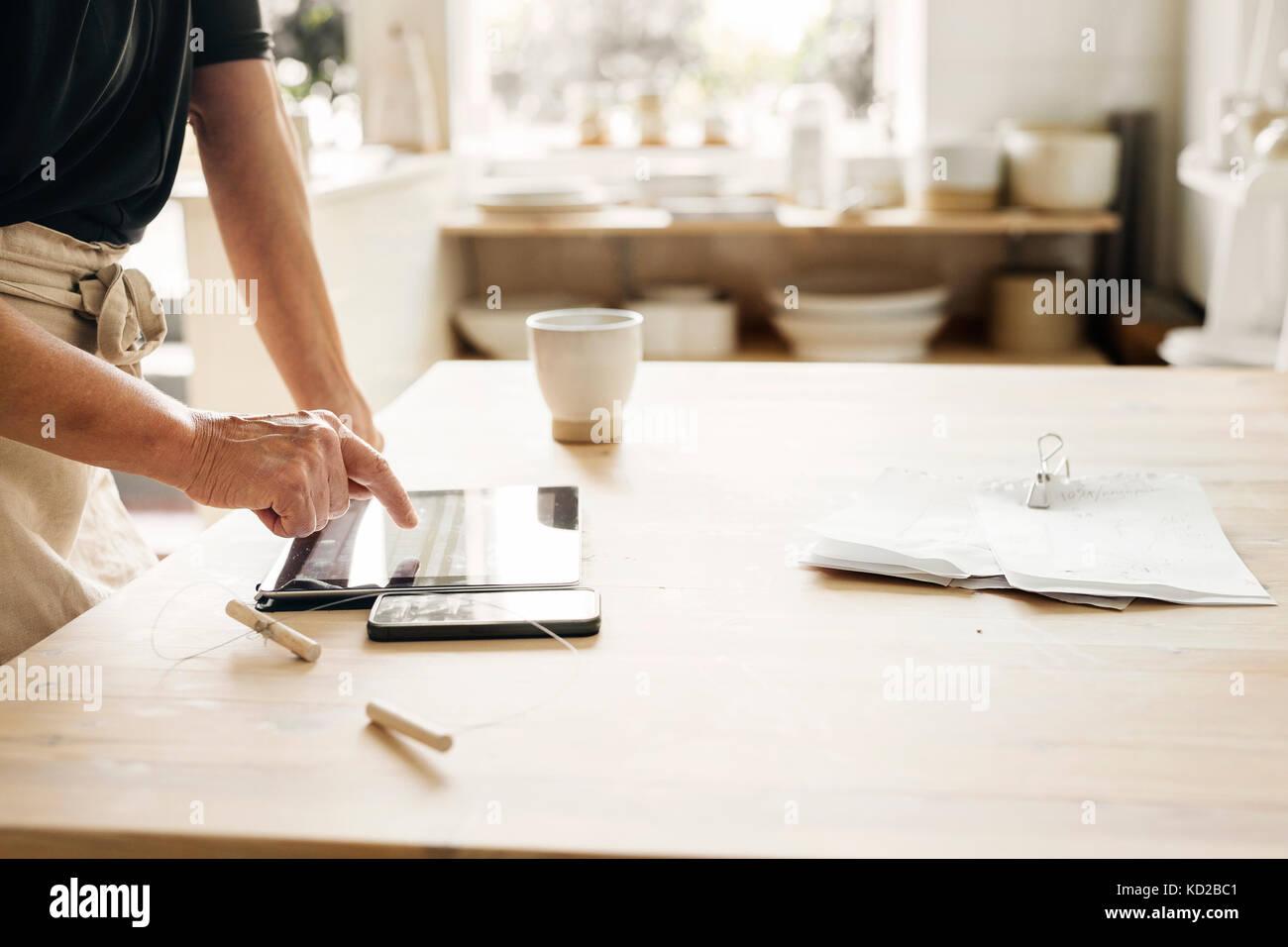 Potter mit digitalen Tablet bei der Arbeit Stockfoto