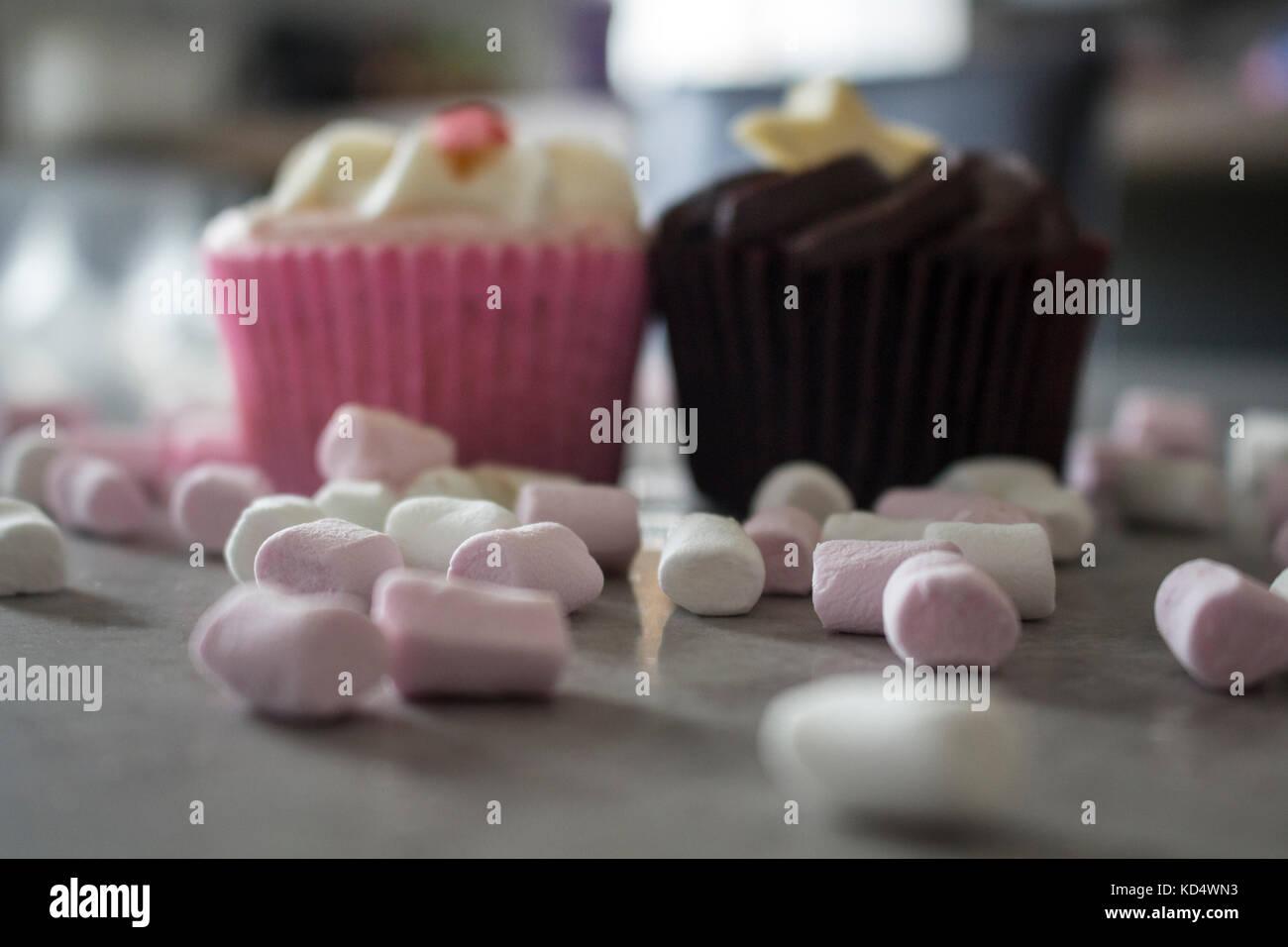 Erdbeer und Schokolade cupcakes durch heiße Schokolade mit Sahne und Schokolade abstauben begleitet. Stockbild