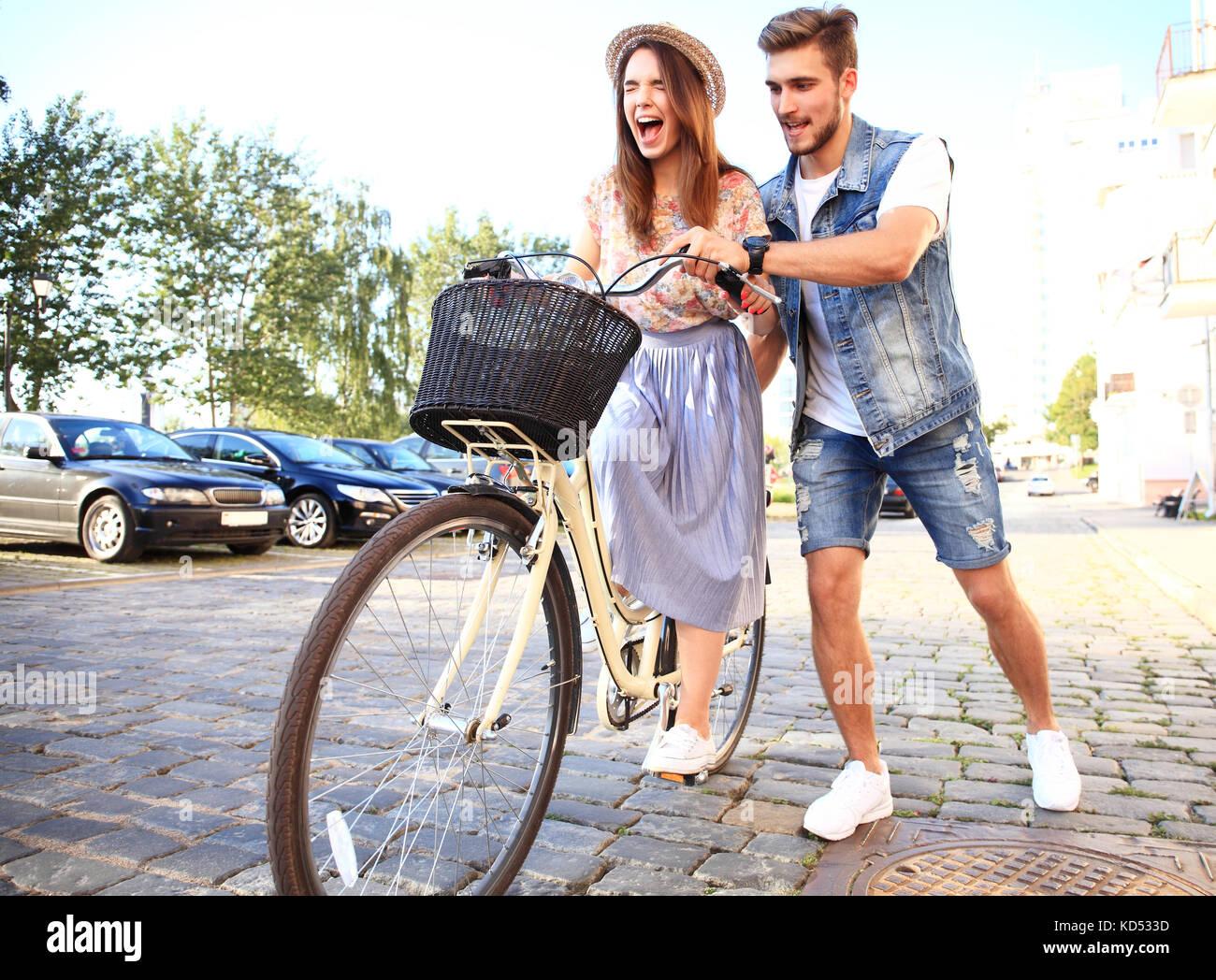 Glückliches junges Paar gehen für eine Fahrt mit dem Fahrrad an einem Sommertag in der Stadt. Sie Spaß Stockbild