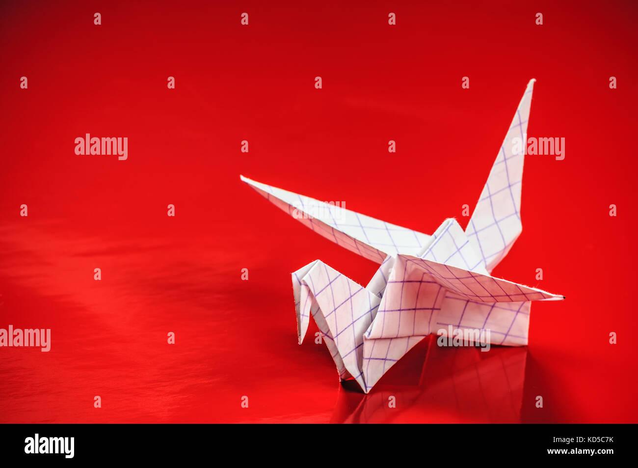 Origami-Kranich auf rotem Grund Stockbild