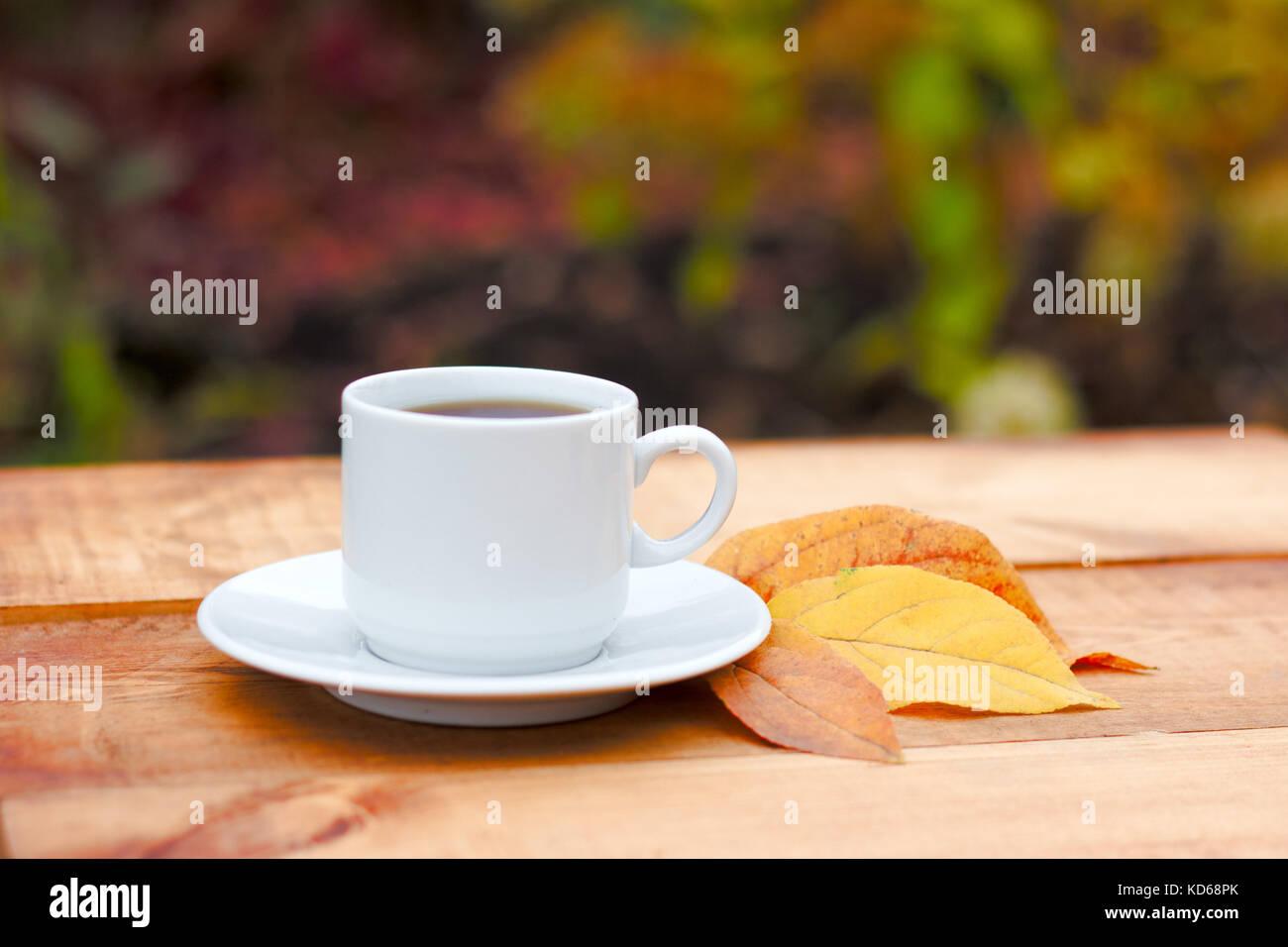 bl tter im herbst und hei dampfende tasse kaffee holztisch gegen goldene bl tter hintergrund. Black Bedroom Furniture Sets. Home Design Ideas