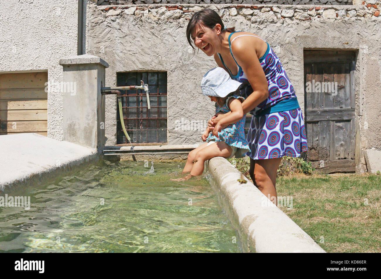 Die Mutter, die ihre Tochter sitzt auf der Kante einer frischen Brunnen Stockfoto
