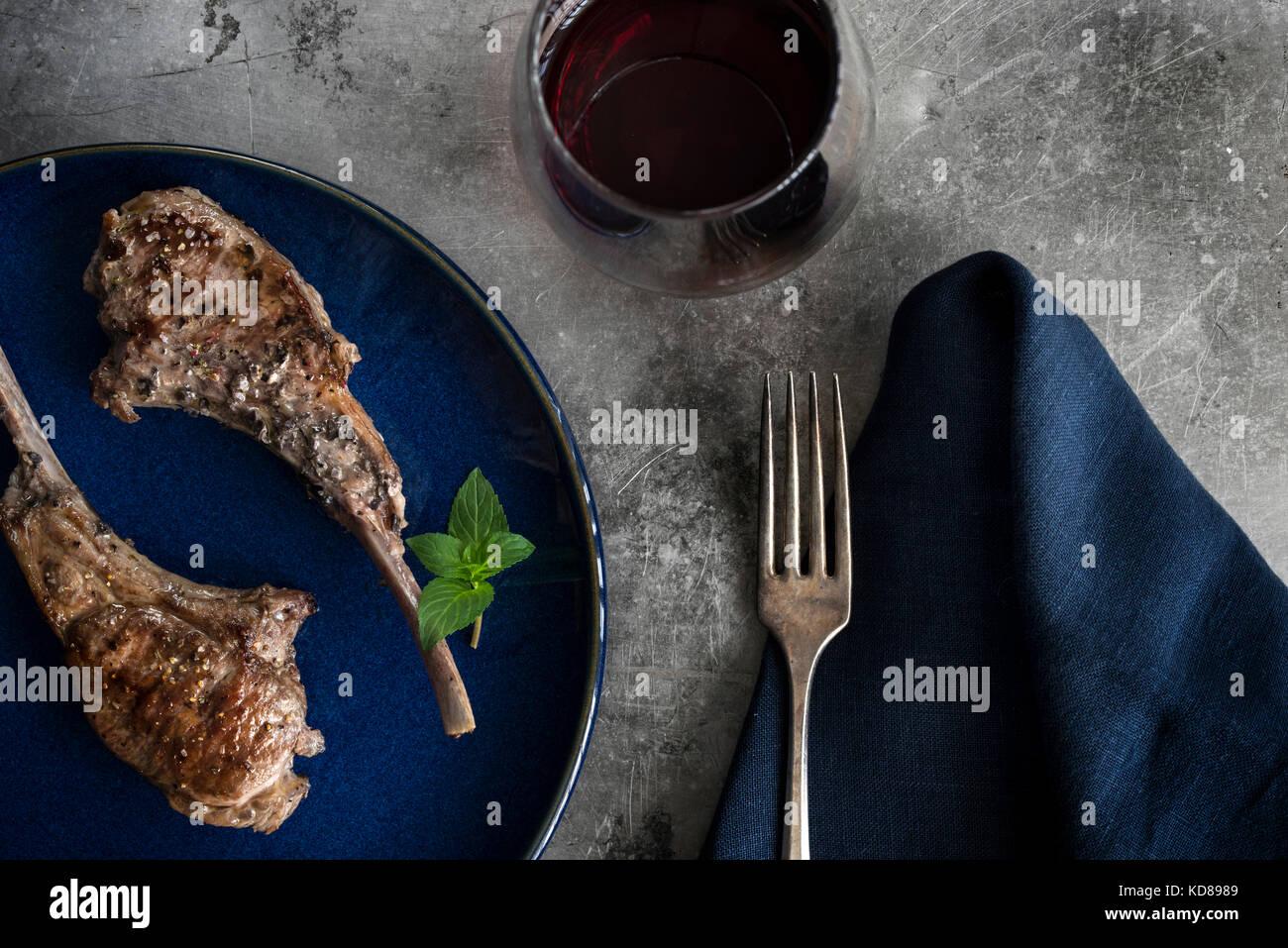 Gebratene lollipop Lammkoteletts auf blauen Platte. Tabelle mit Marine Bettwäsche, Rotwein und rustikale Oberfläche Stockbild