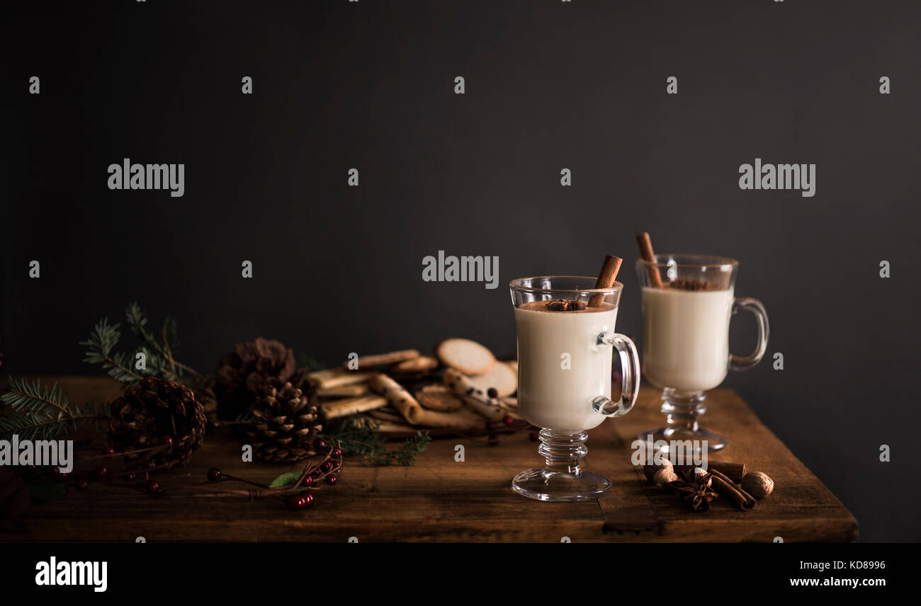 2 Gläser Eierlikör auf einem Holztisch mit festlichen Dekorationen gegen eine feste graue Wand. Stockbild