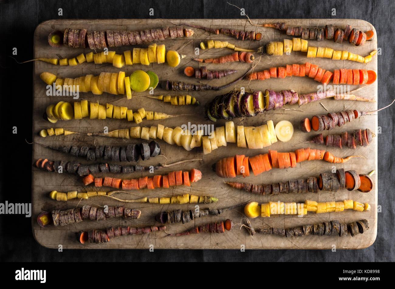 Ein Array von Rainbow Karotten in vielen Formen und Farben, alle fein auf einen verschlissenen Holz Hackklotz gehackt. Stockbild