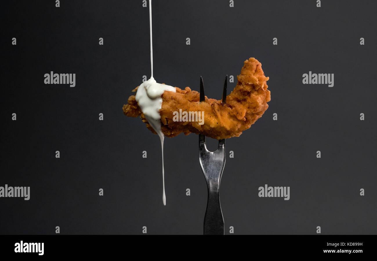 Huhn Ausschreibung auf Gabel mit Tropfen der Ranch Sauce. grauer Hintergrund Stockbild