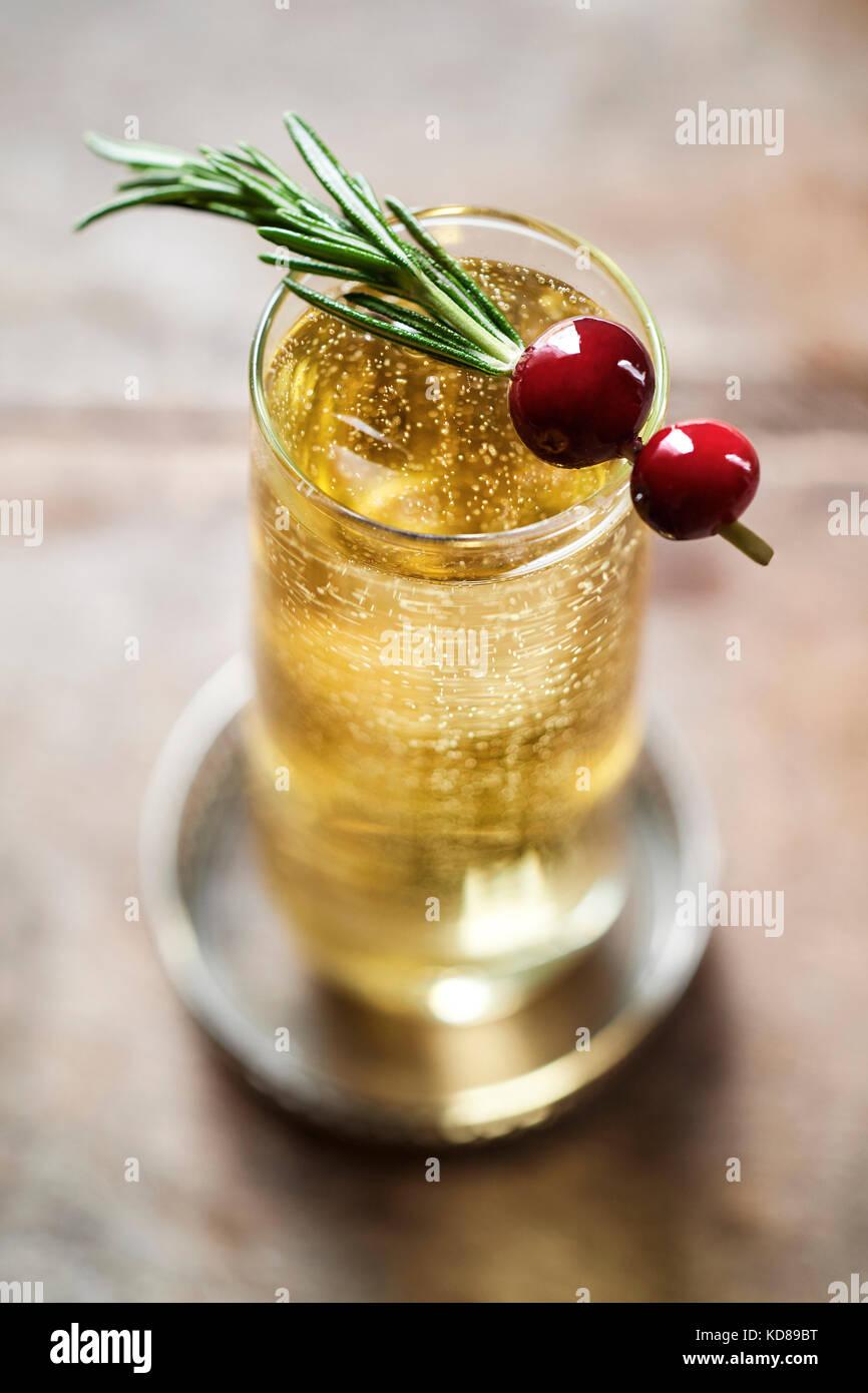 Schönen Champagner zu trinken, Blubbern in der stielhöhlung Flöte mit Rosmarin und Cranberry garnieren. Stockbild