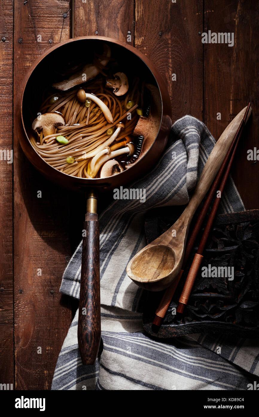 Alte Welt Kupfer Topf mit asiatische Nudelsuppe und Pilze auf reiche Holzoberfläche mit antikem Holz, Löffel Stockbild