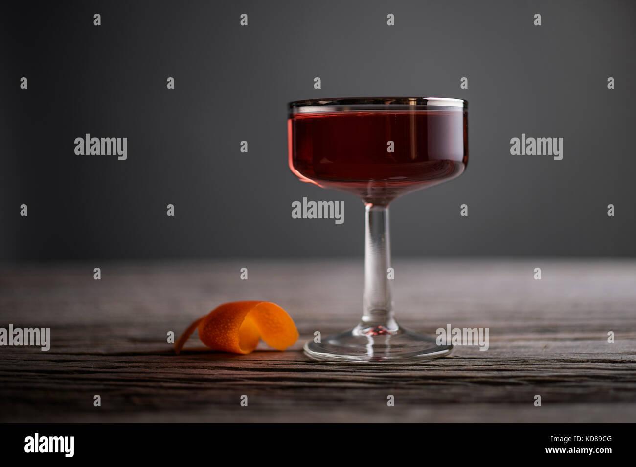 Anspruchsvolle Cocktail in einem Jahrgang, Silber ausgekleidet, coupé Glas mit Orange Peel auf einem urigen, Stockbild
