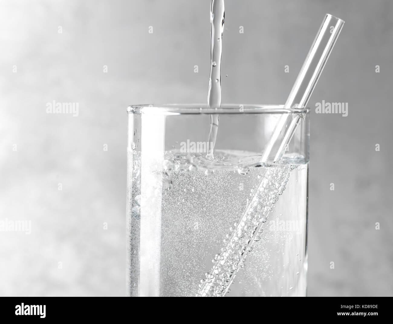 Detail der funkelnden Wasser in ein Glas mit einer durchsichtigen Strohhalm auf grauem Hintergrund aus Metall gegossen Stockbild