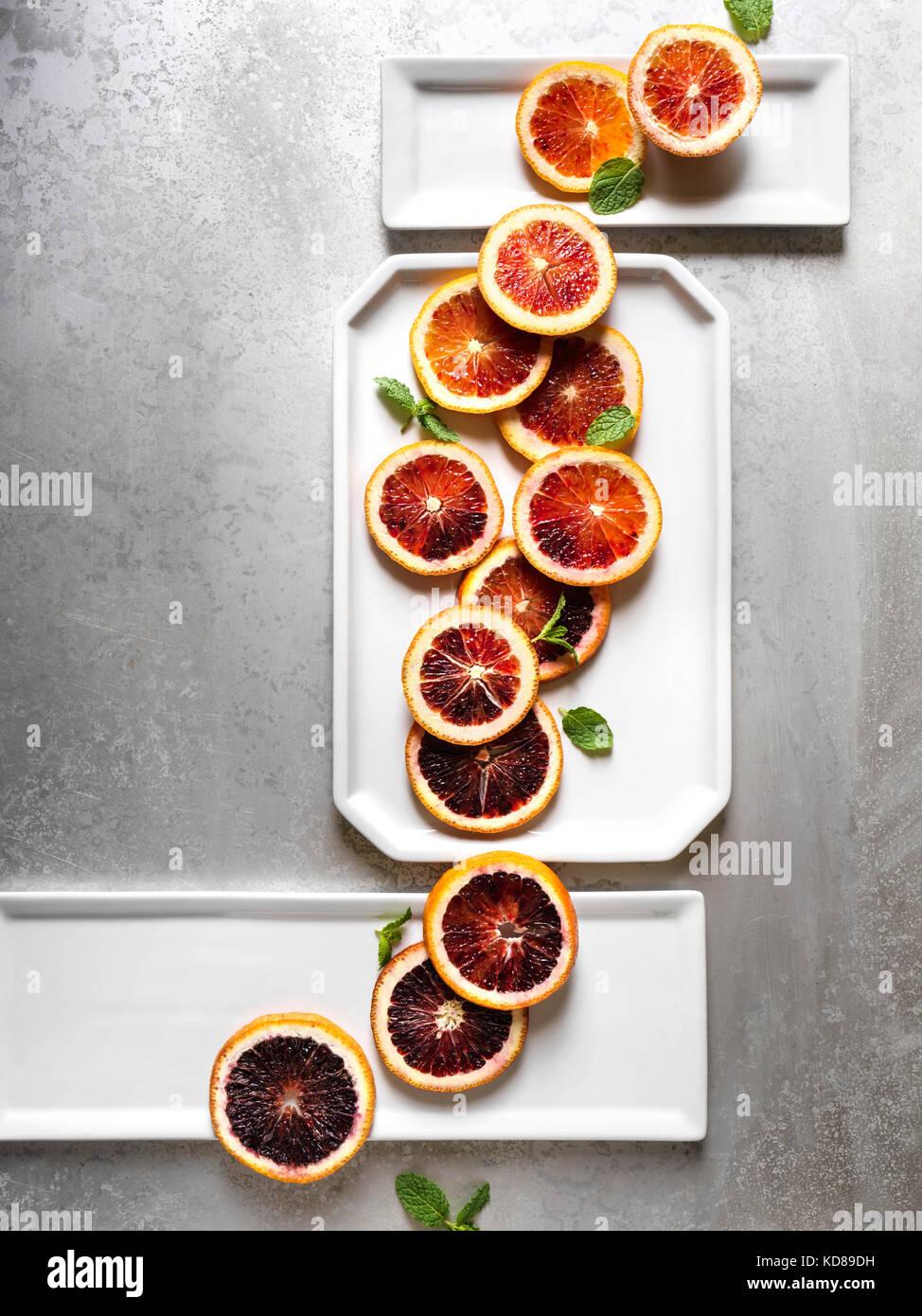 Blut Orangenscheiben im künstlerischen Form über weiße Platten und texturierte Oberfläche aus Stockbild