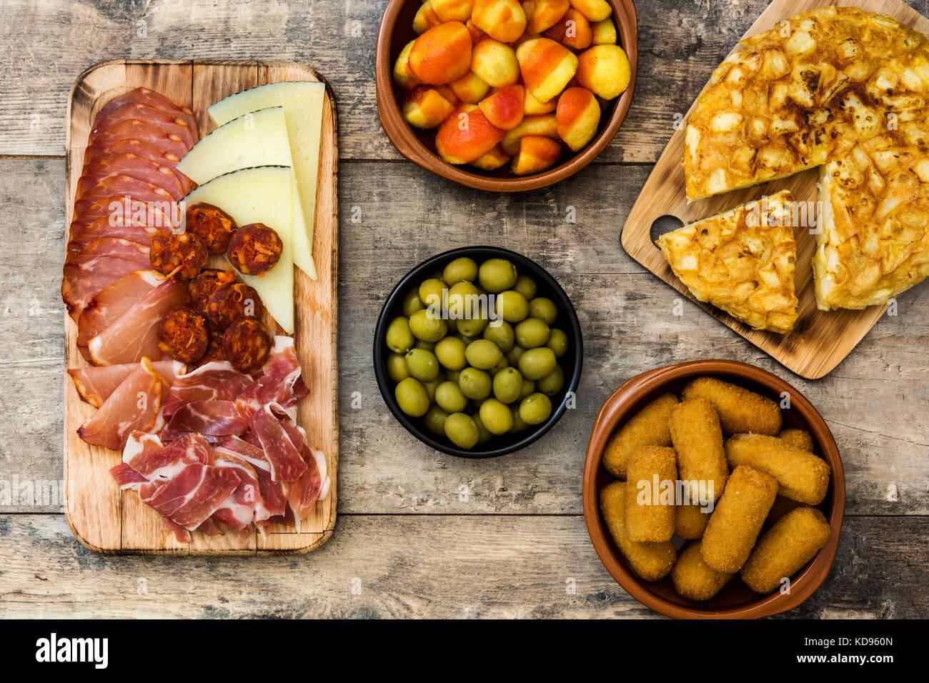 Traditionelle spanische Tapas. Kroketten, Oliven, Omelettes, Schinken und Patatas Bravas auf hölzernen Tisch Stockbild