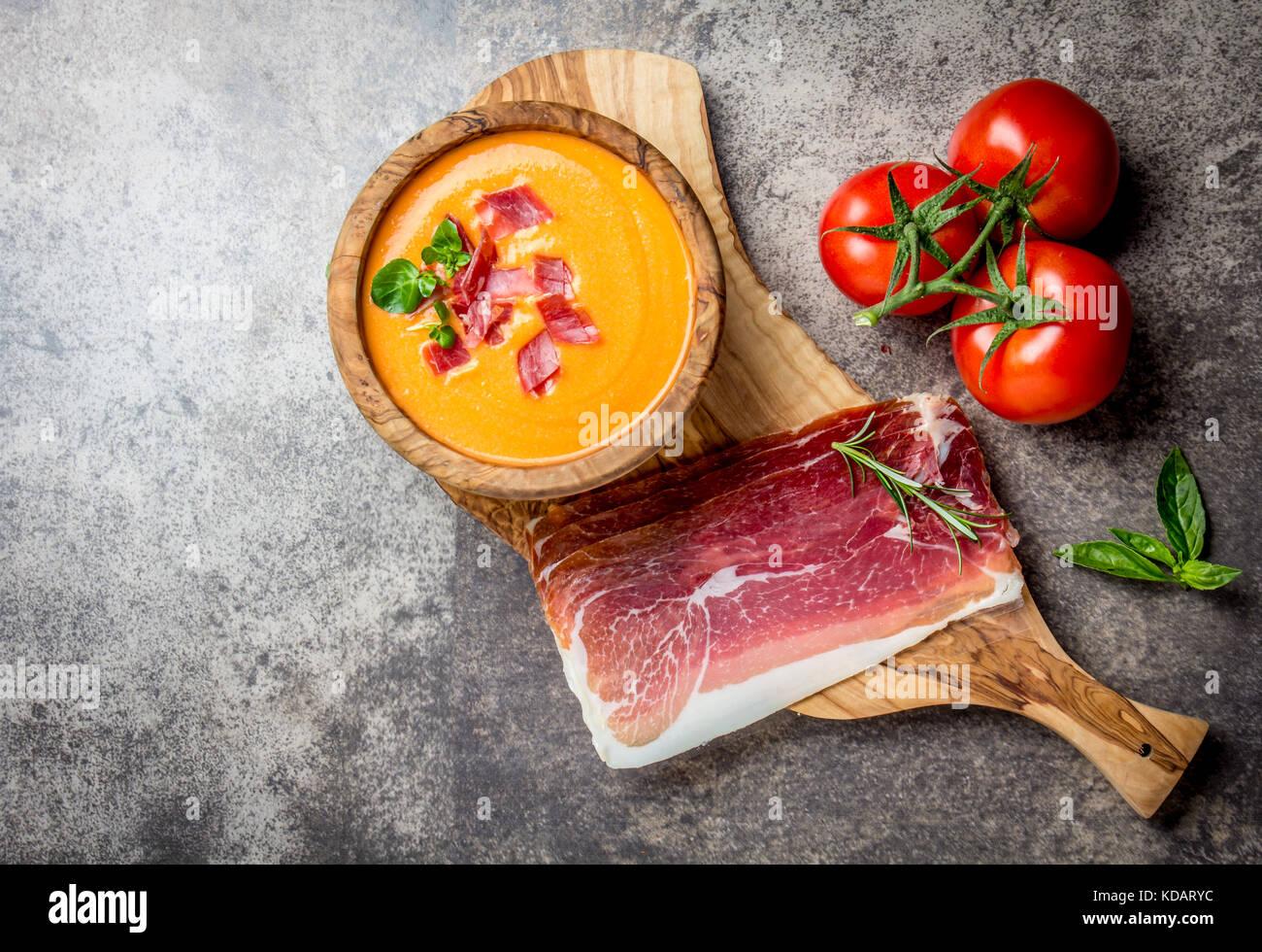 Spanische Tomatensuppe Salmorejo serviert in Olivenöl hölzerne Schüssel mit Schinken Jamón Serrano Stockbild