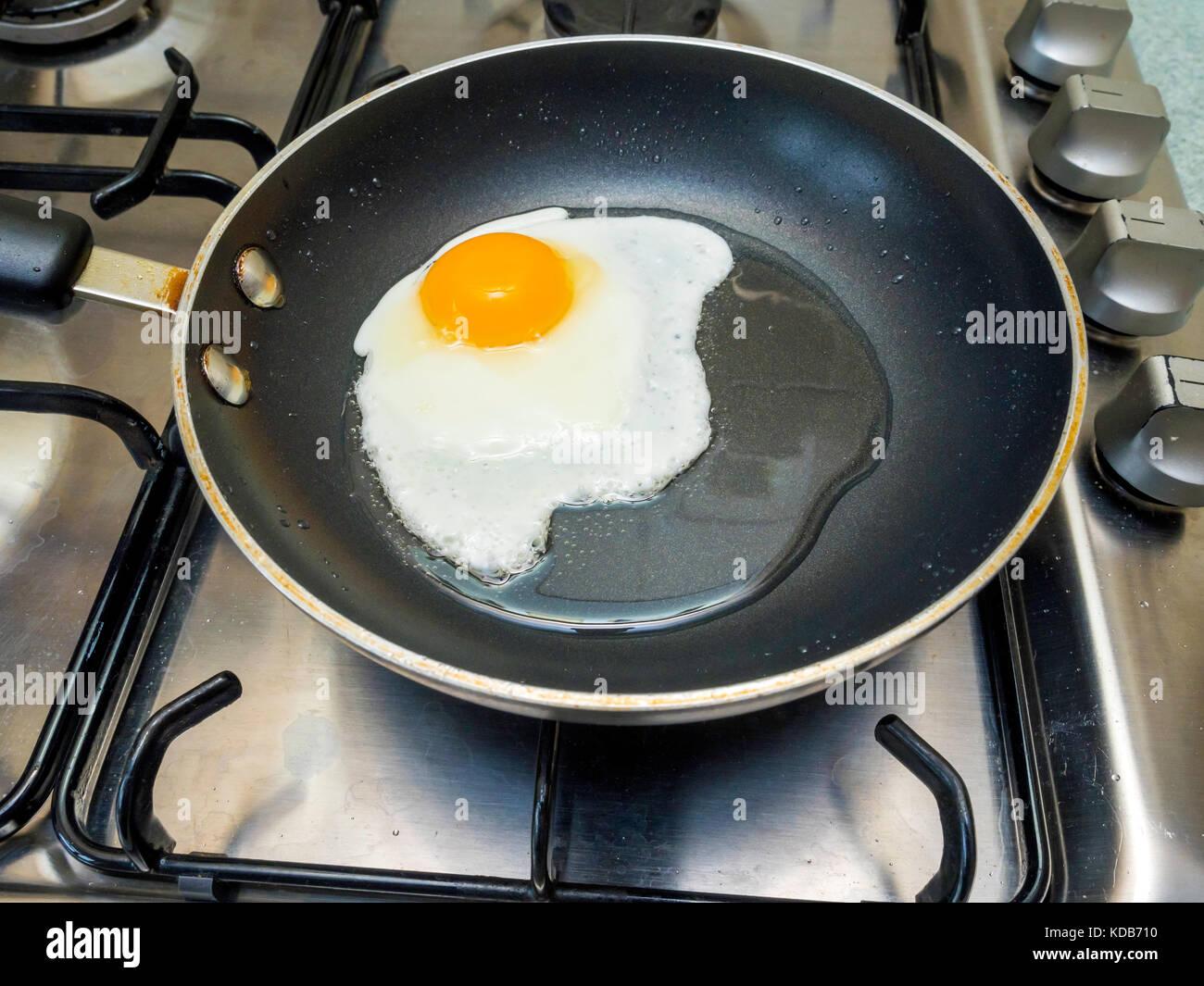 Ein Ei wird in Sonnenblumenöl in einem kleinen Teflon beschichtete antihaftbeschichtete Pfanne auf dem Gasherd Stockbild