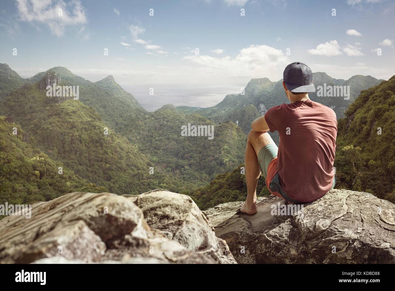 Junger Mann hat einen Panoramablick auf einer tropischen Landschaft Stockbild
