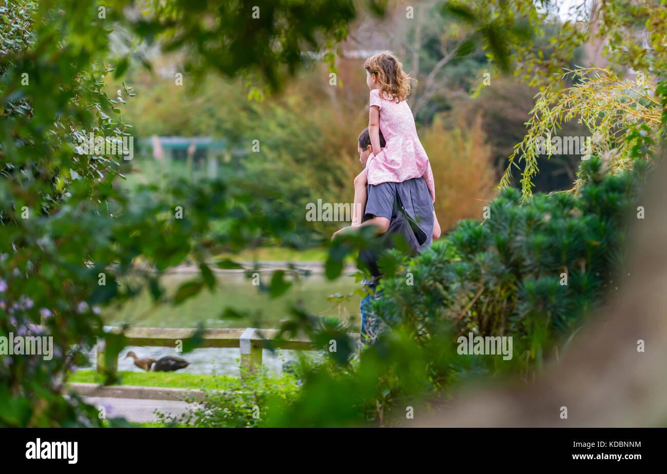 Junge Mädchen, die auf den Schultern eines Mannes, eine piggy zurück fahren, durch einen Park in Großbritannien. Stockbild