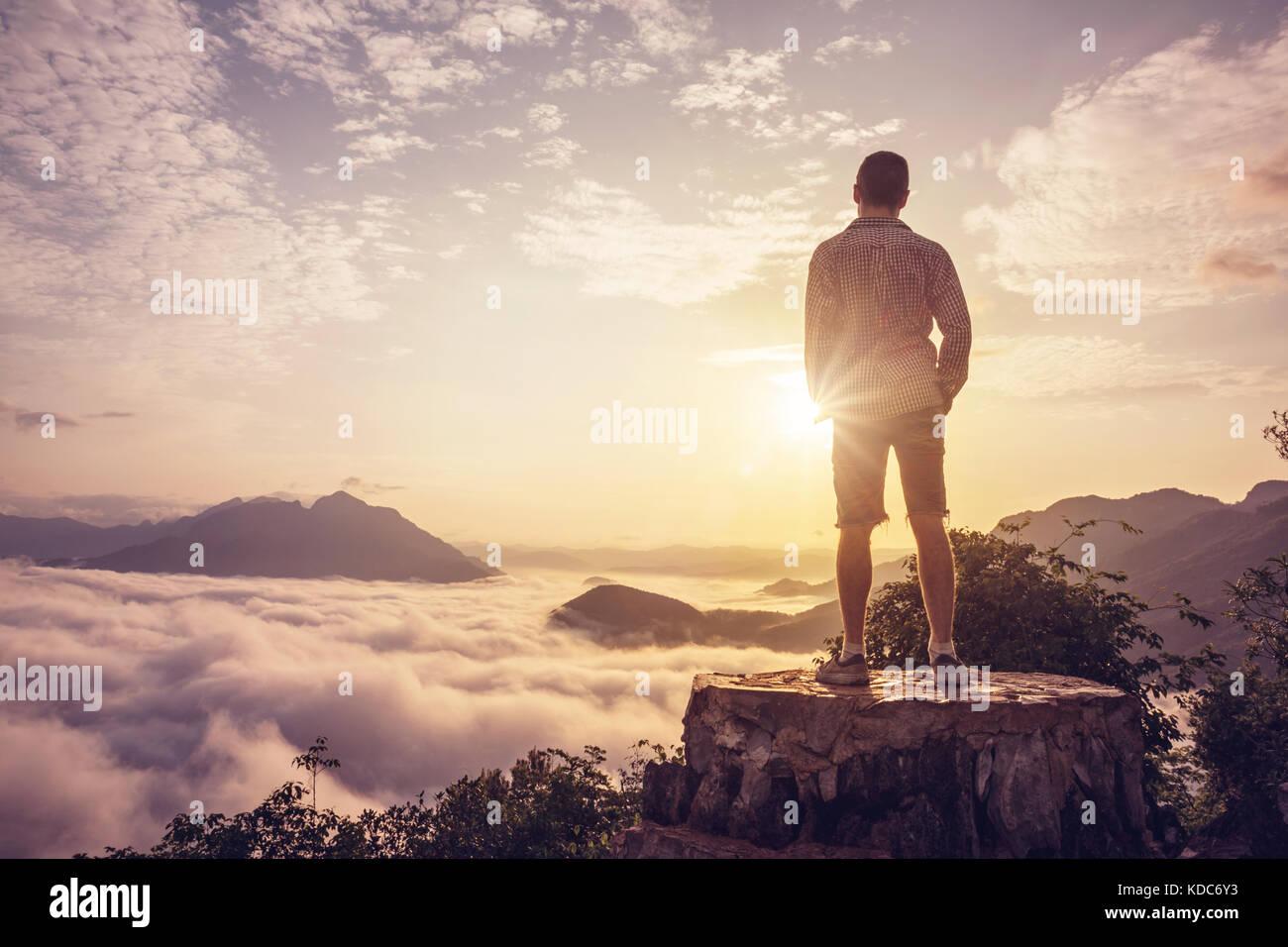 Mann auf einem Gipfel über den Wolken Stockbild