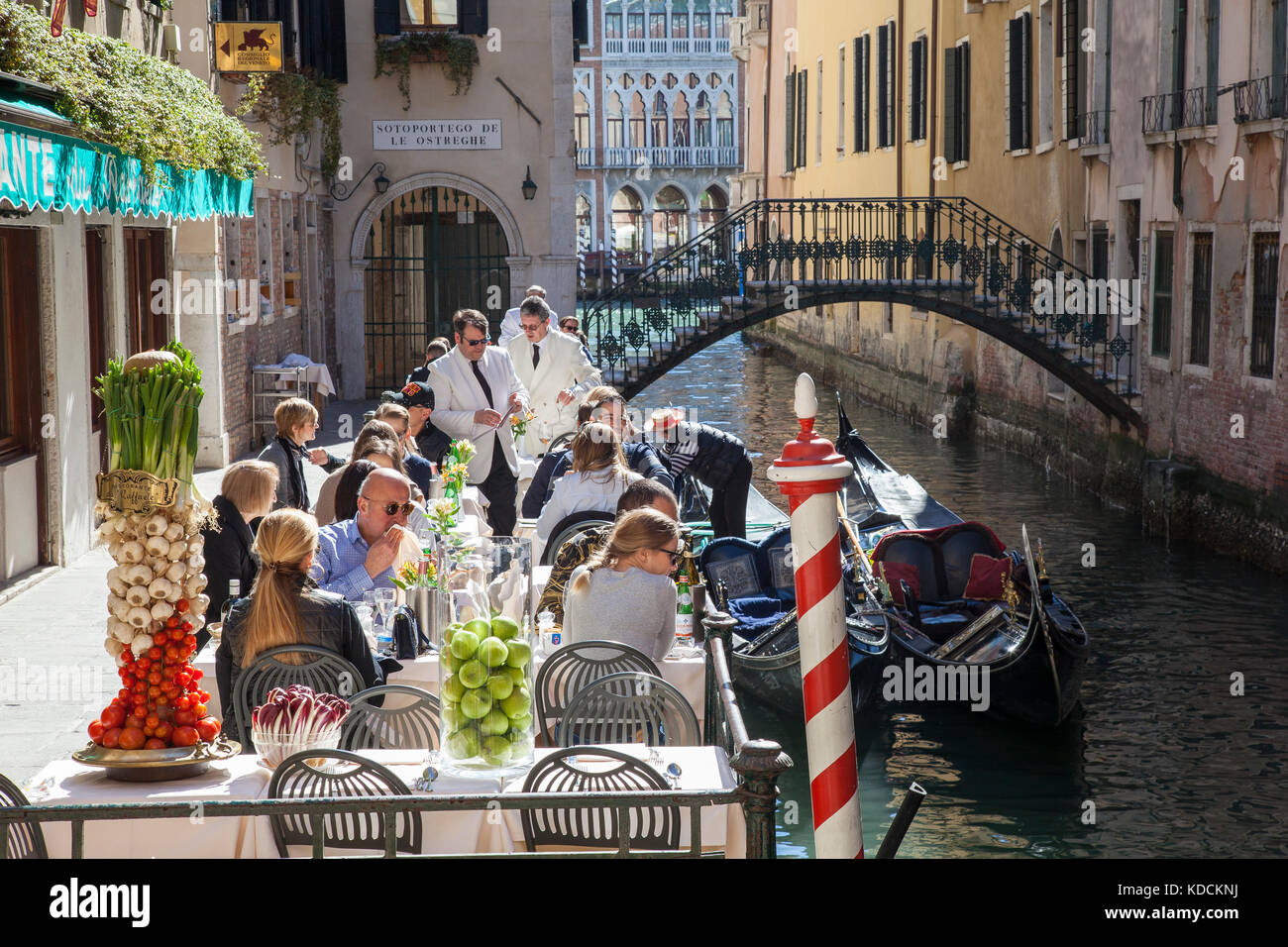 Touristen im beliebten Ristorante da Raffaele, San Marco, Venedig, Italien neben einem Kanal mit Gondeln und Gondoliere Stockbild