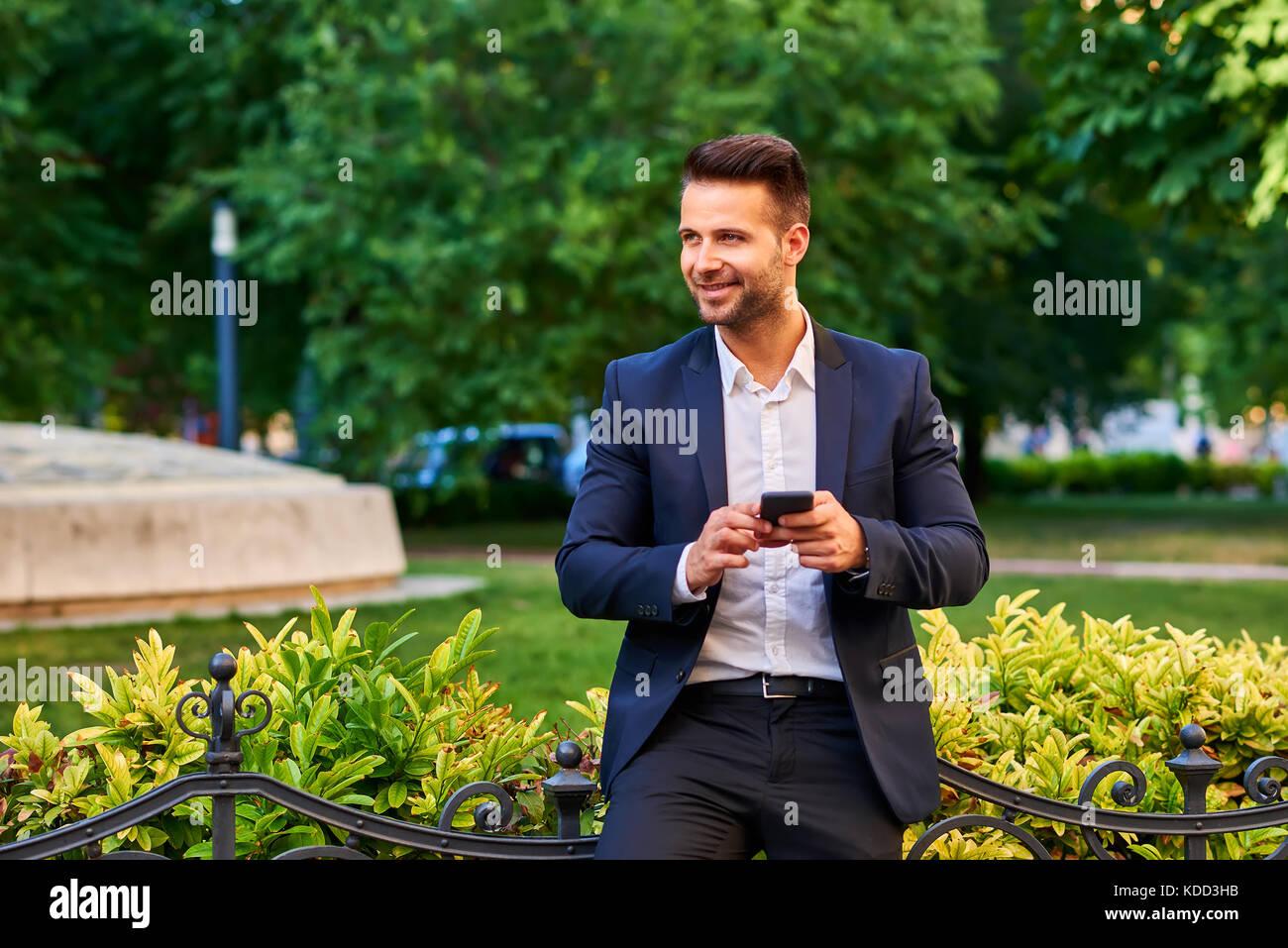 Ein schöner junger Geschäftsmann, der sich in einem Park gegen den Zaun lehnt und dabei sein Smartphone hält Stockfoto